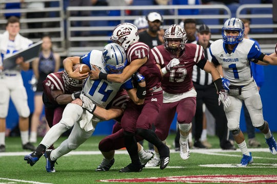 Calallen's Matt Castro (41) helps make a tackle against Austin McCallum.
