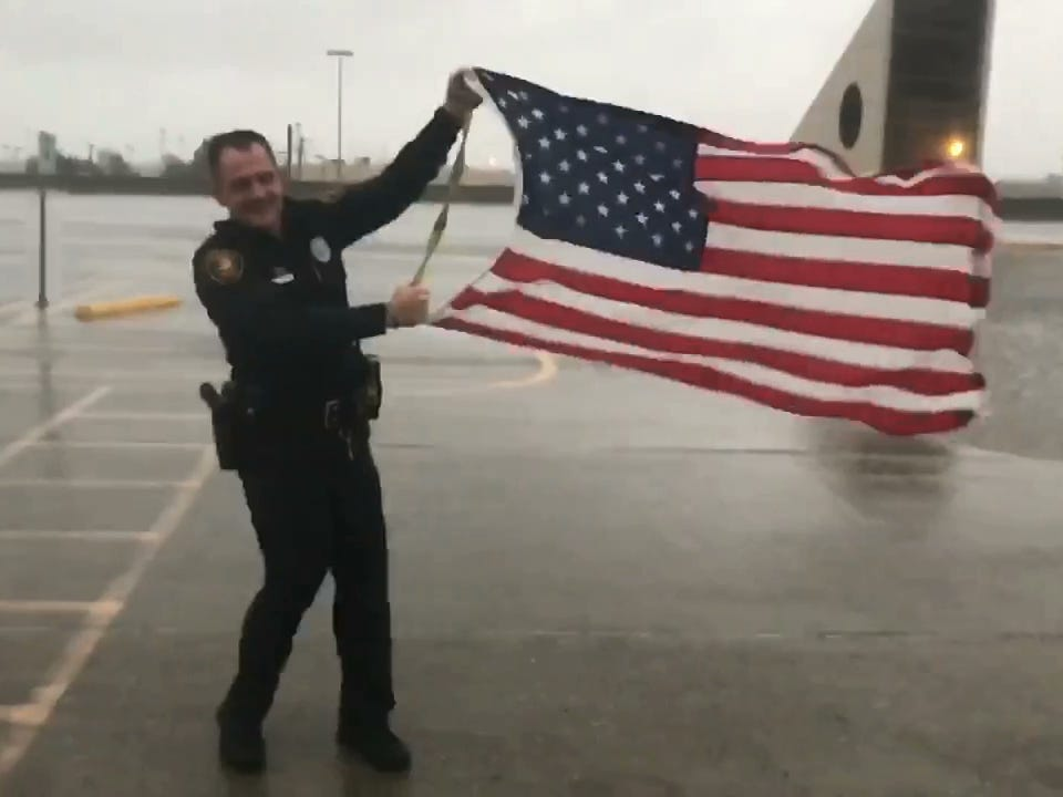 A Corpus Christi police officer holds up an American Flag on the La Palmera parking garage.