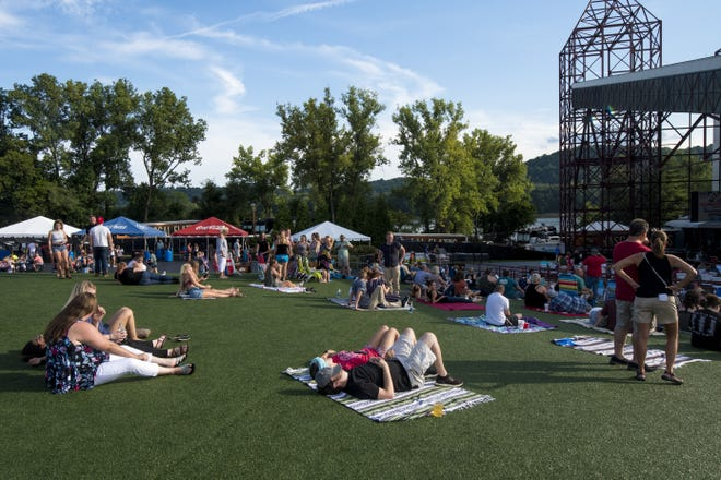 Early arrivals sunbathe before the opening acts for a Rascal Flatts performance at Riverbend Music Center