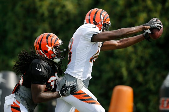 Cincinnati Bengals wide receiver A.J. Green (18) follows through the end zone with a catch ahead of cornerback Davontae Harris (35) during a training camp practice at the Paul Brown Stadium training facility in downtown Cincinnati on Monday, Aug. 6, 2018.