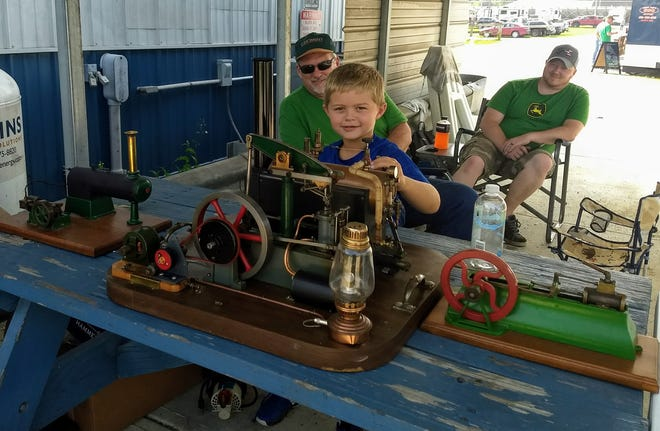 "Lucas Egbert, 8, of Williamsburg, blows the whistle on Grandpa Bruce's model of a Walking Beam steam engine. The original is in England. When asked why he had a model, Grandpa Egbert replied, ""Because I can't own the big one."" Egbert is a member of the Ohio Valley Antique Machinery Association and has attended that group's antique machinery show all 48 years. This year's show runs Aug. 9-12 in Georgetown."
