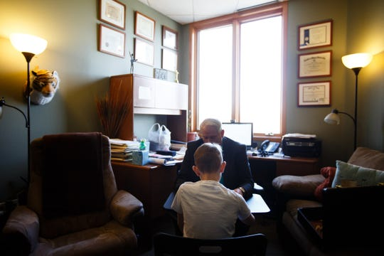 Sam Barlage goes through an exercise with Psychologist David Grove at Compass Clinical Associates on Thursday, March 8, 2018, in Urbandale. Sam, 10, has serious mental illness, including bipolar disorder which hinders him from focusing on a given task. Dr. Grove lets him take breaks by playing basketball to help him do what he wants him to accomplish.