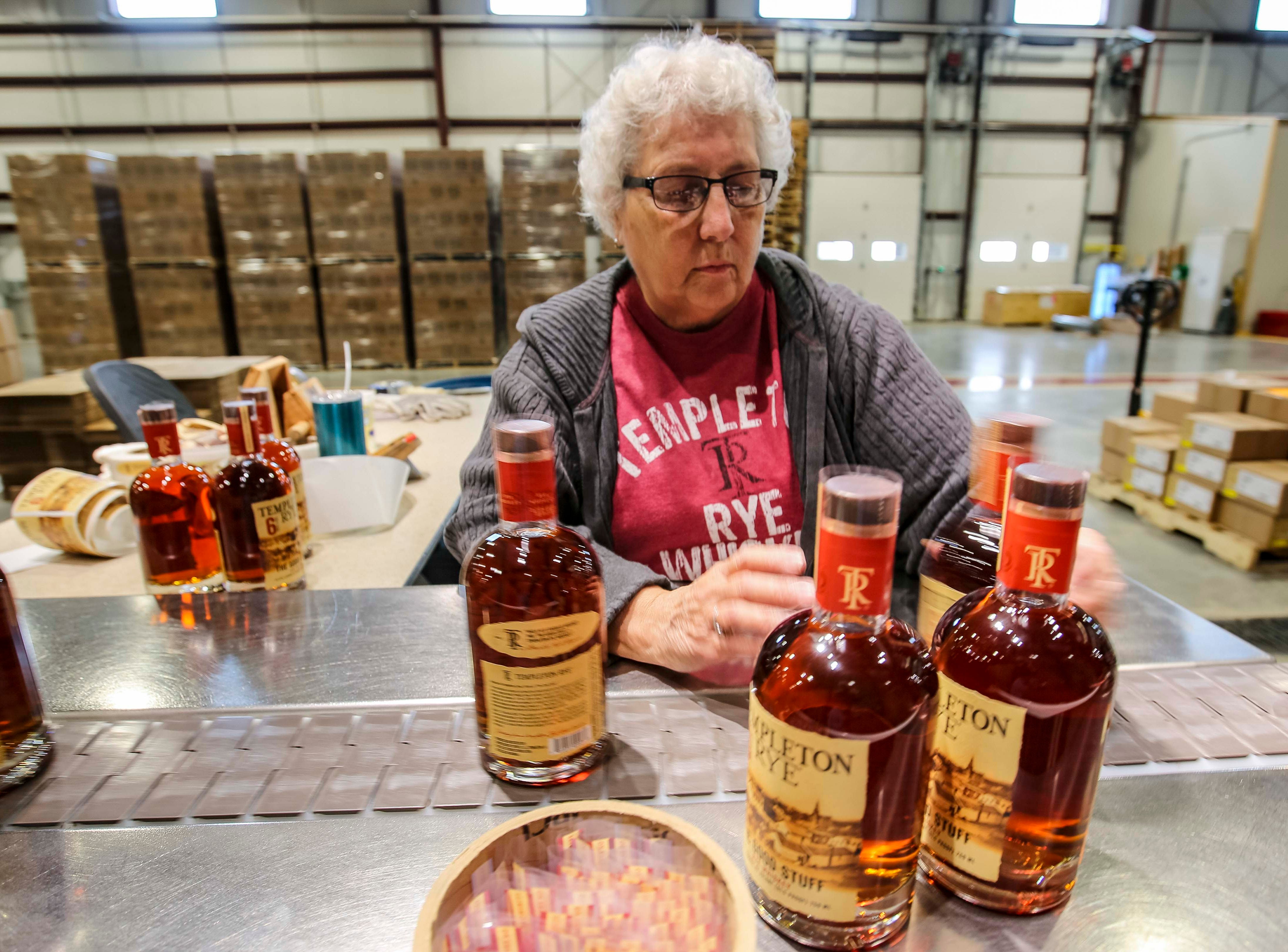 Diane Gute adjusts labels on bottles of Templeton Rye in their new $35 million distillery in Templeton, Iowa, shown here Monday, Aug. 6, 2018, featuring a museum and visitor's center.