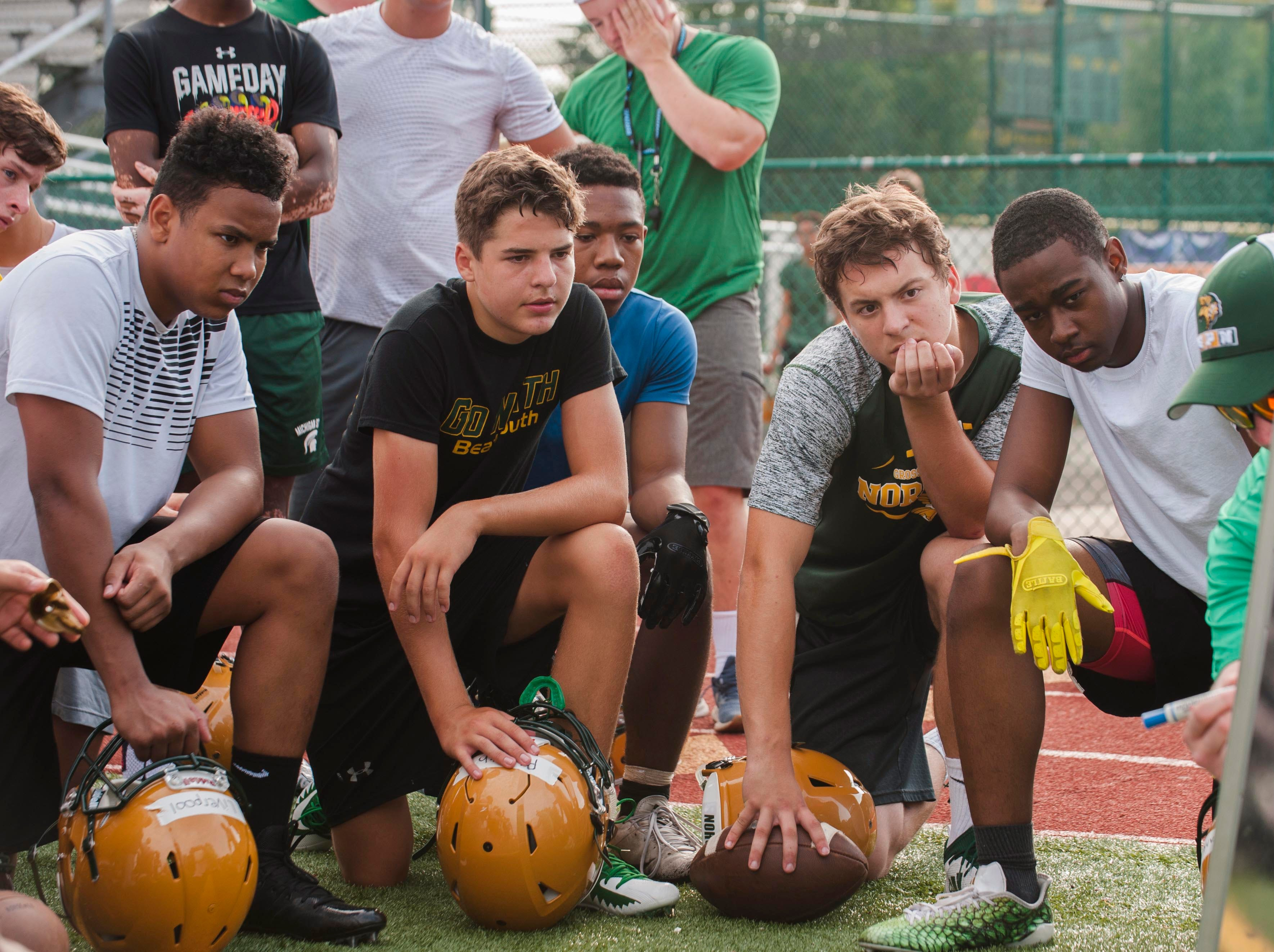 Grosse Pointe North players, including (left to right, front row) Jason Liverpool, Joe Plieth, Brendan Cwiklinski, and Joaquin Franklin watch and listen as assistant head coach/offensive coordinator Dennis Pascoe draws up a play on a white board.