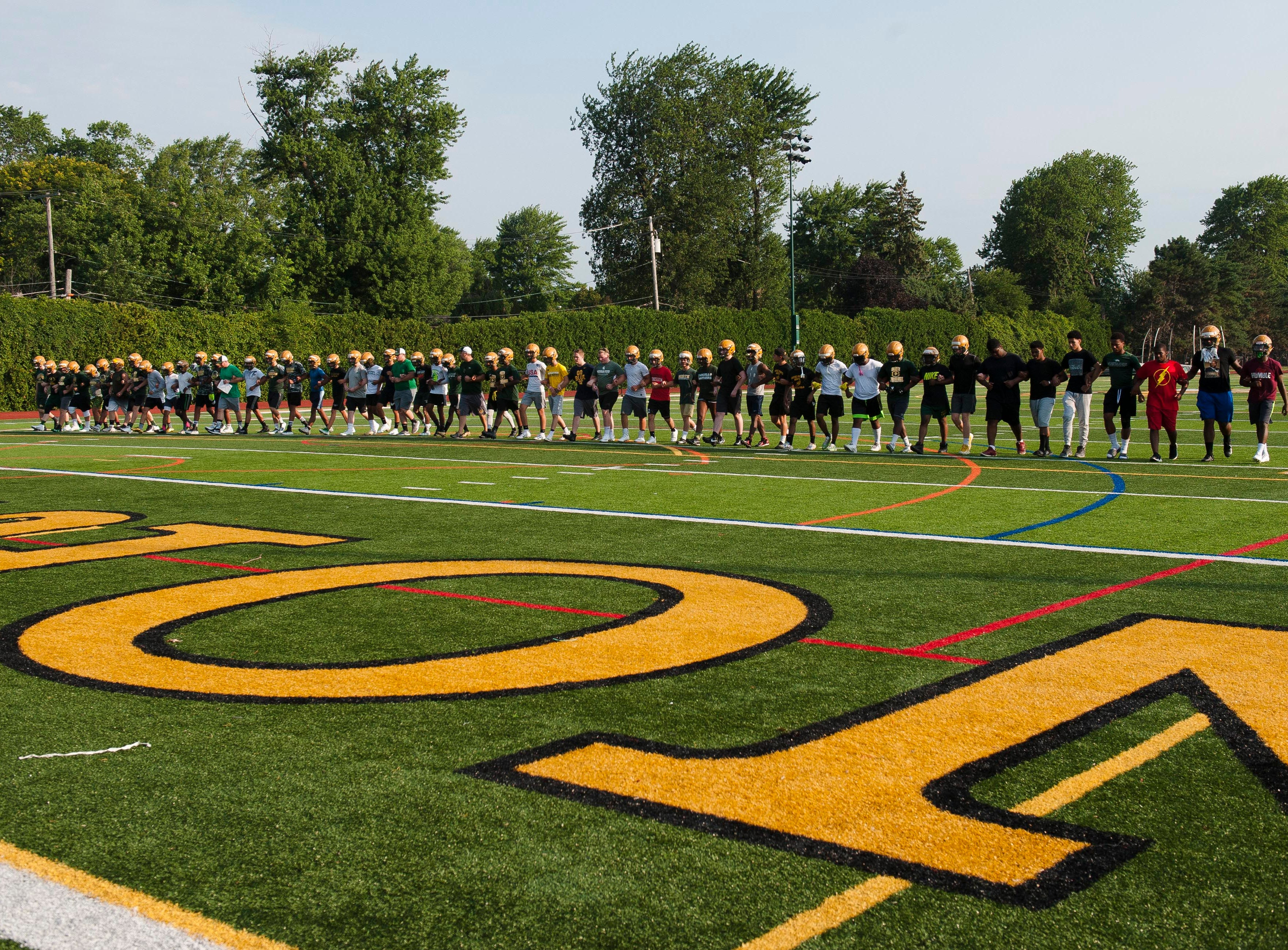 Led by new head coach Joe Drouin, the entire Grosse Pointe North football team walks the length of the field arm-in-arm in a unity exercise at the start of the team's first practice of the season.
