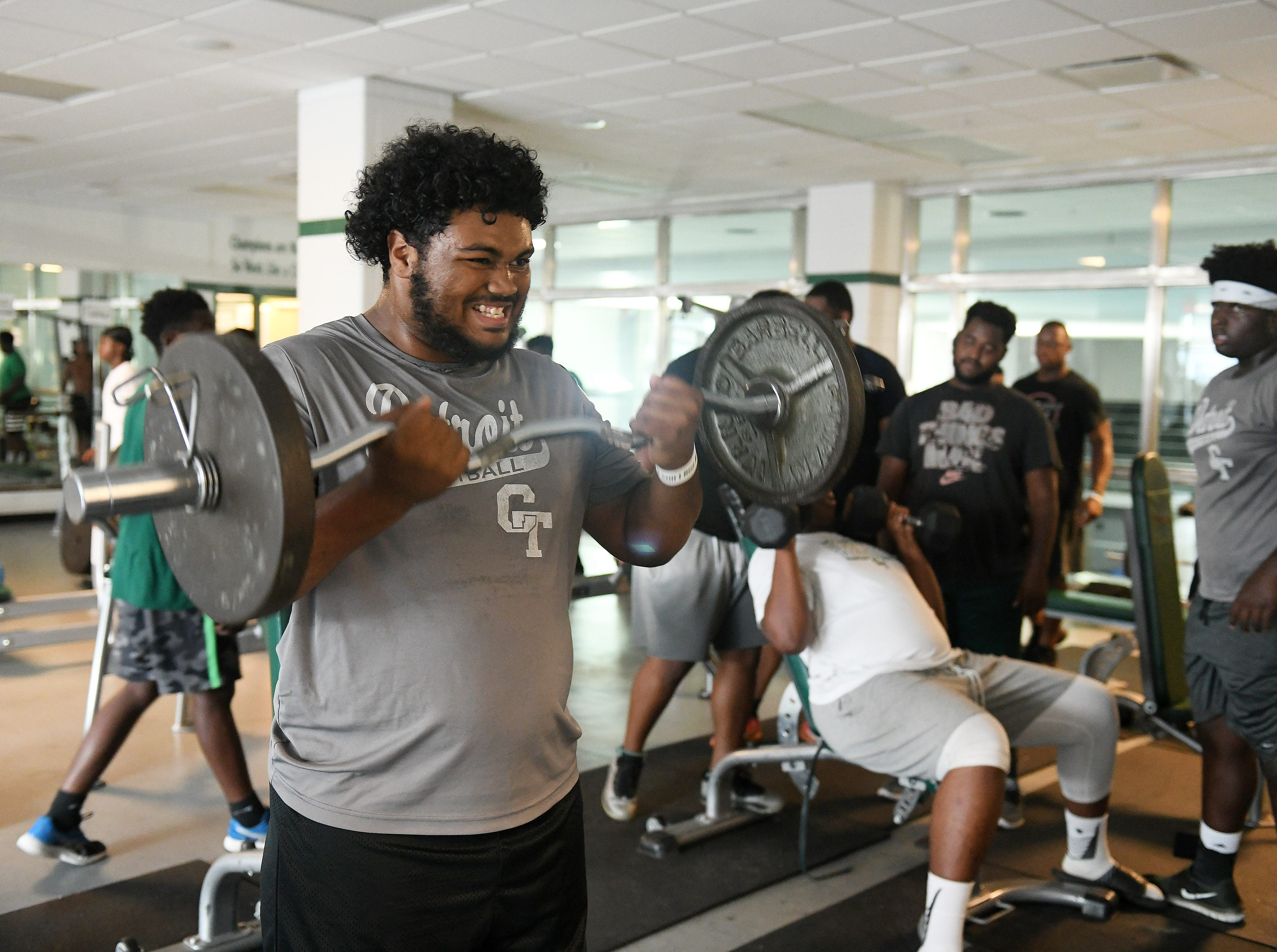 Detroit Cass Tech senior defensive tackle and nose guard Jaylen Billings does curls during weight lifting before football practice.