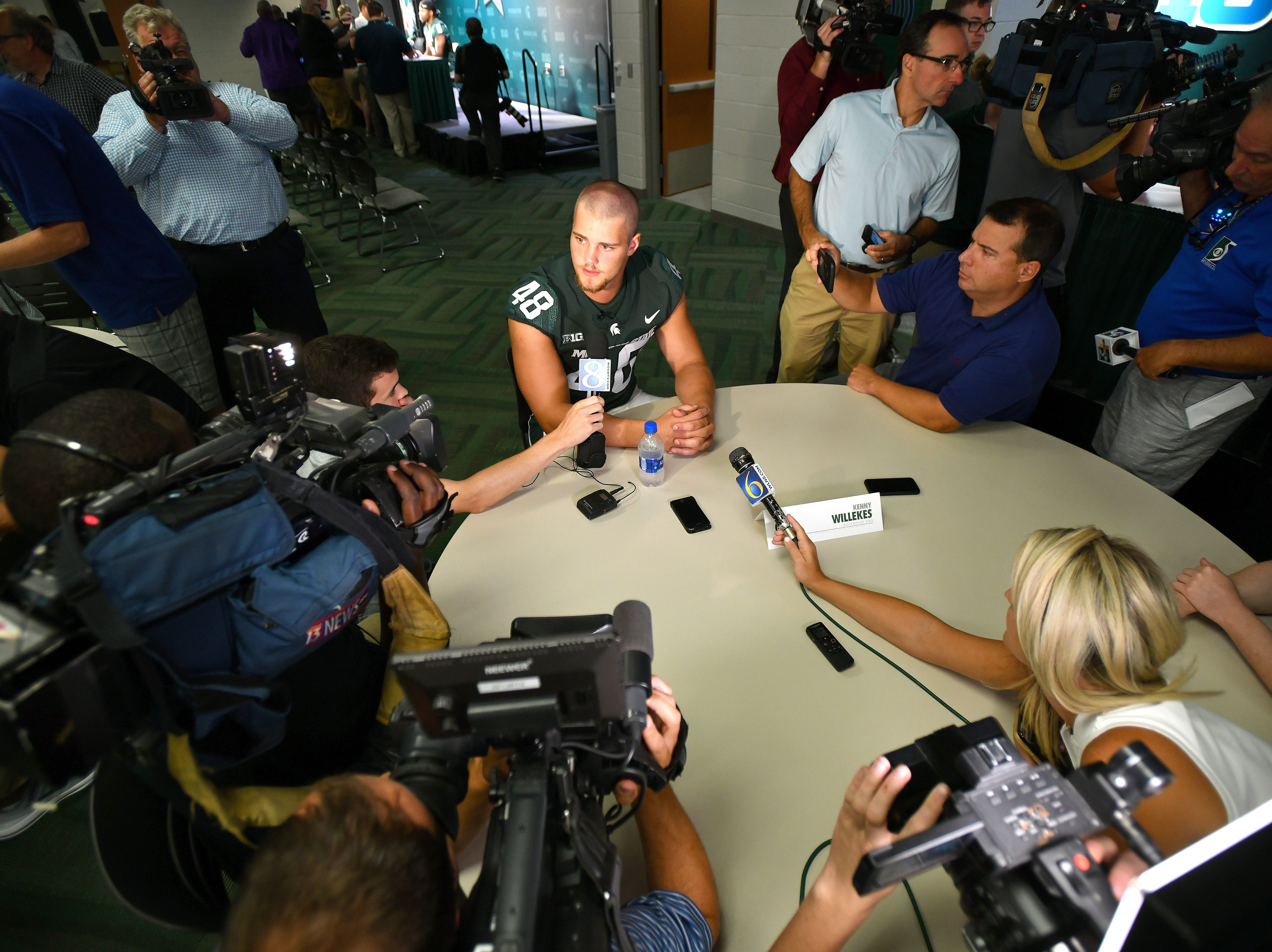 Michigan State defensive end Kenny Willekes is surrounded by the media at his table.