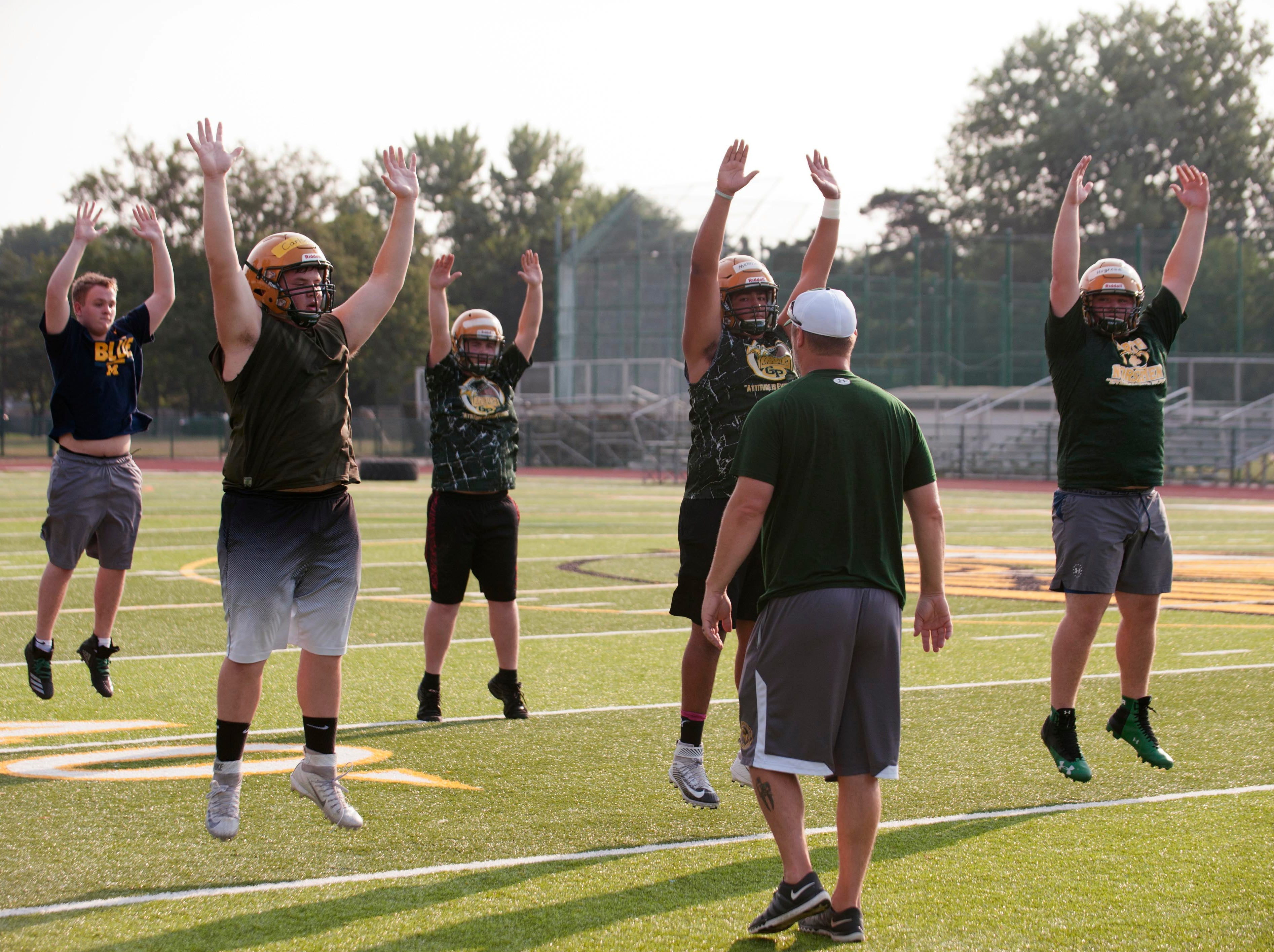 Grosse Pointe North head coach Joe Drouin has the linemen jumping early during the first practice of the season.