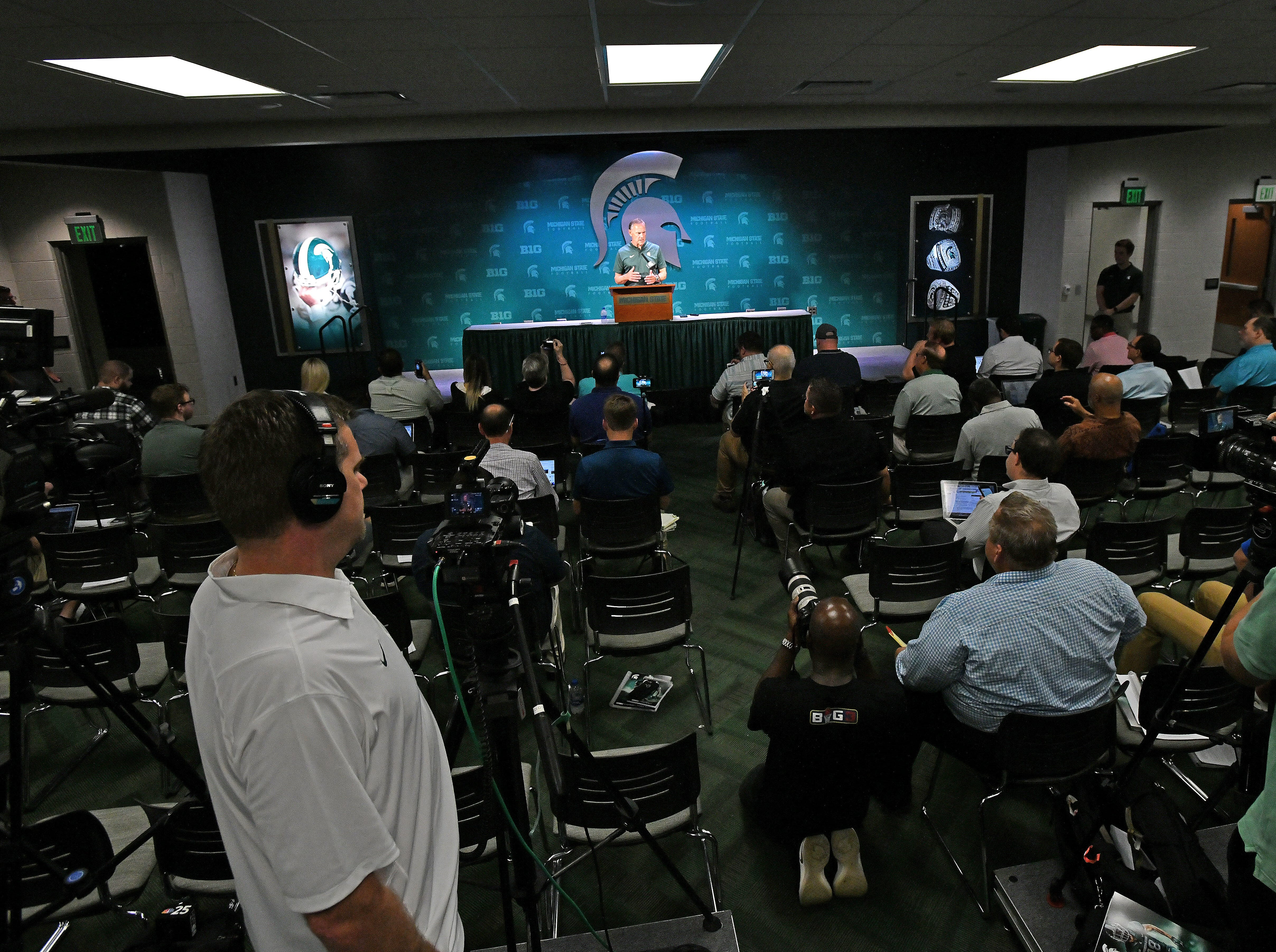 Cameras and reporters clutter the Tom and Lupe Izzo Family Media Center as Mark Dantonio takes the podium in Spartan Stadium.