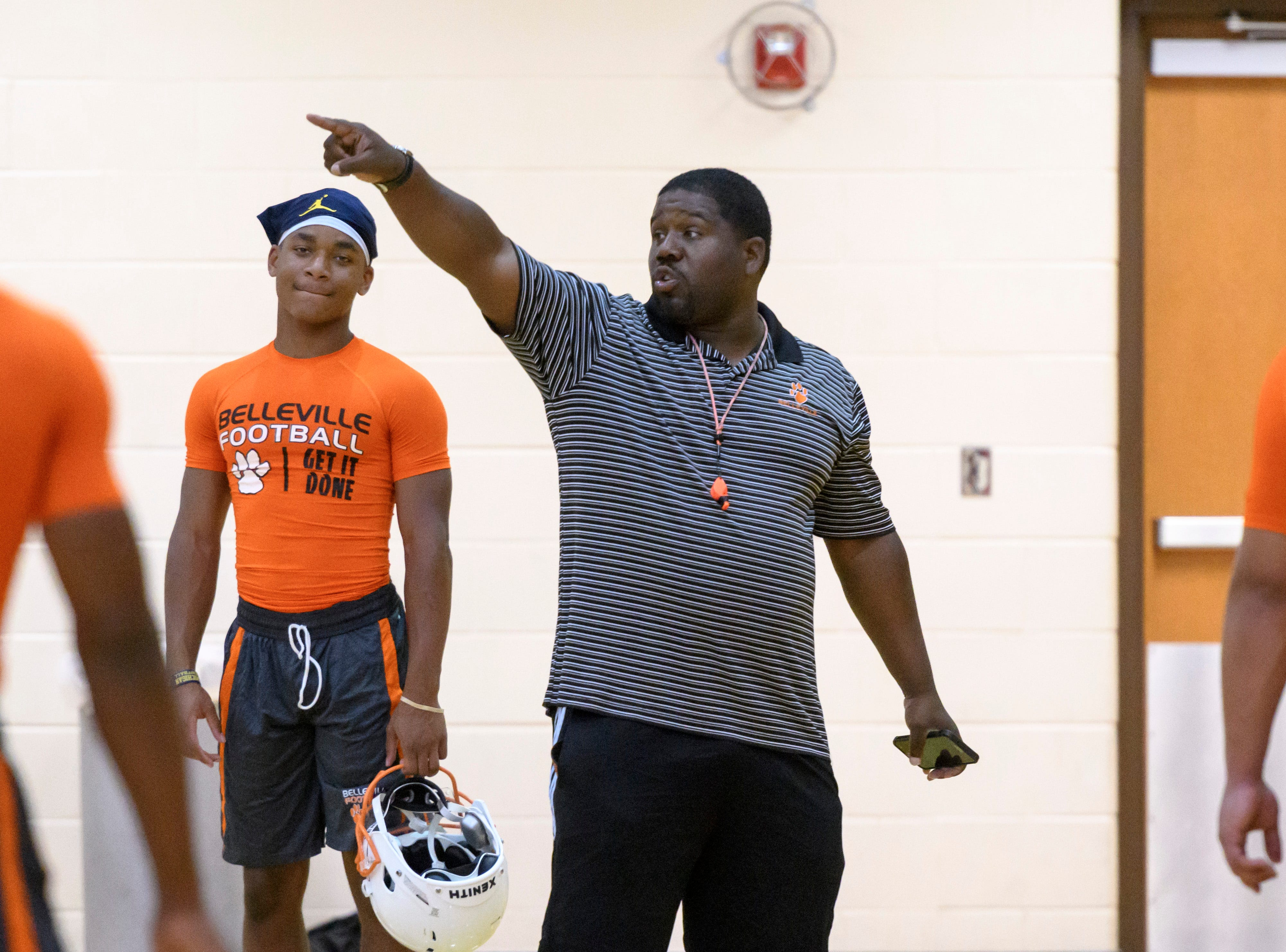 Belleville head football coach Jermain Crowell gives directions to his players during the team's first practice of the season in the gym.