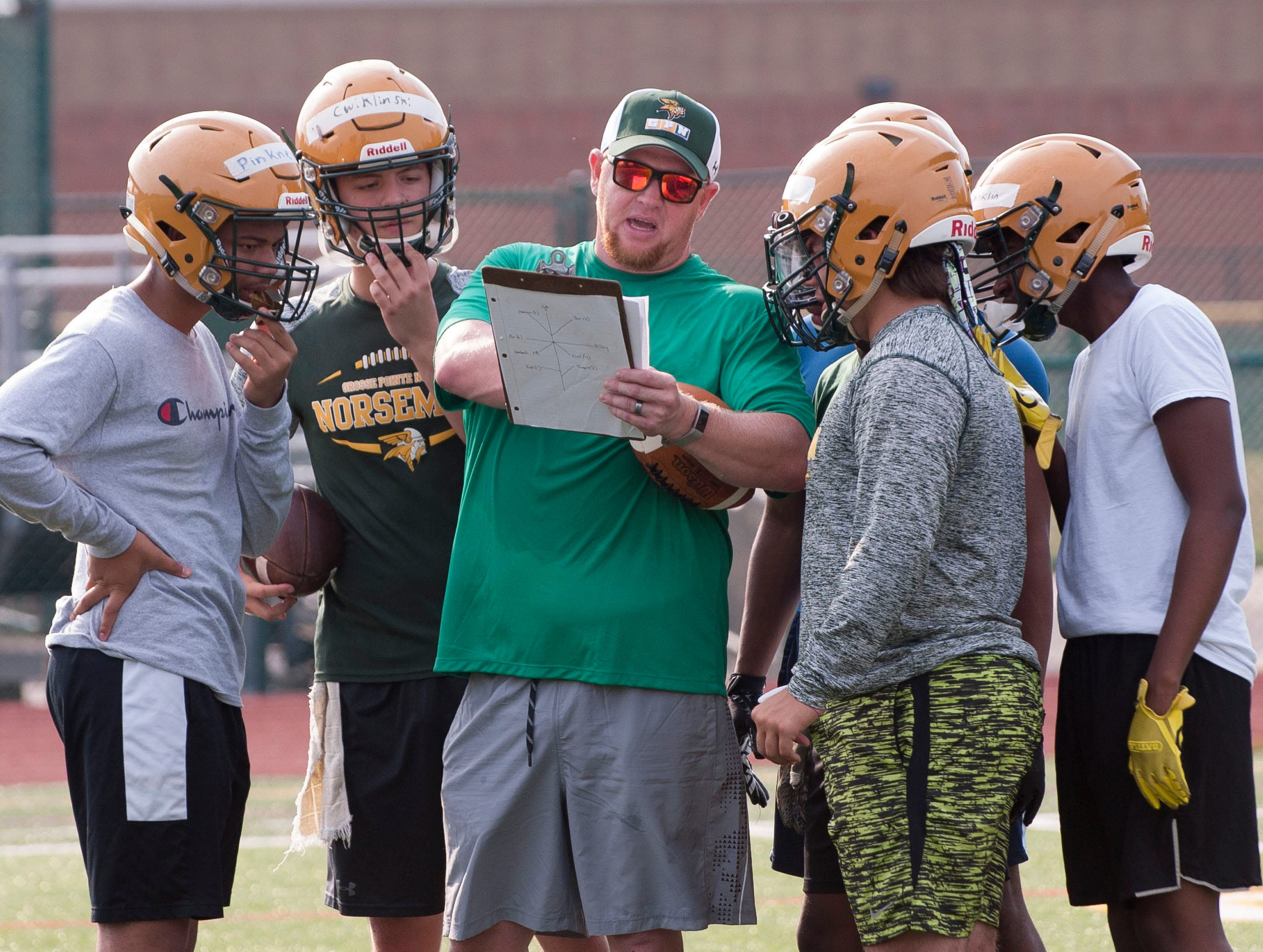 Grosse Pointe North assistant head coach/offensive coordinator Dennis Pascoe huddles up the offense and calls a play during the Norsemen's first practice of the season Monday.