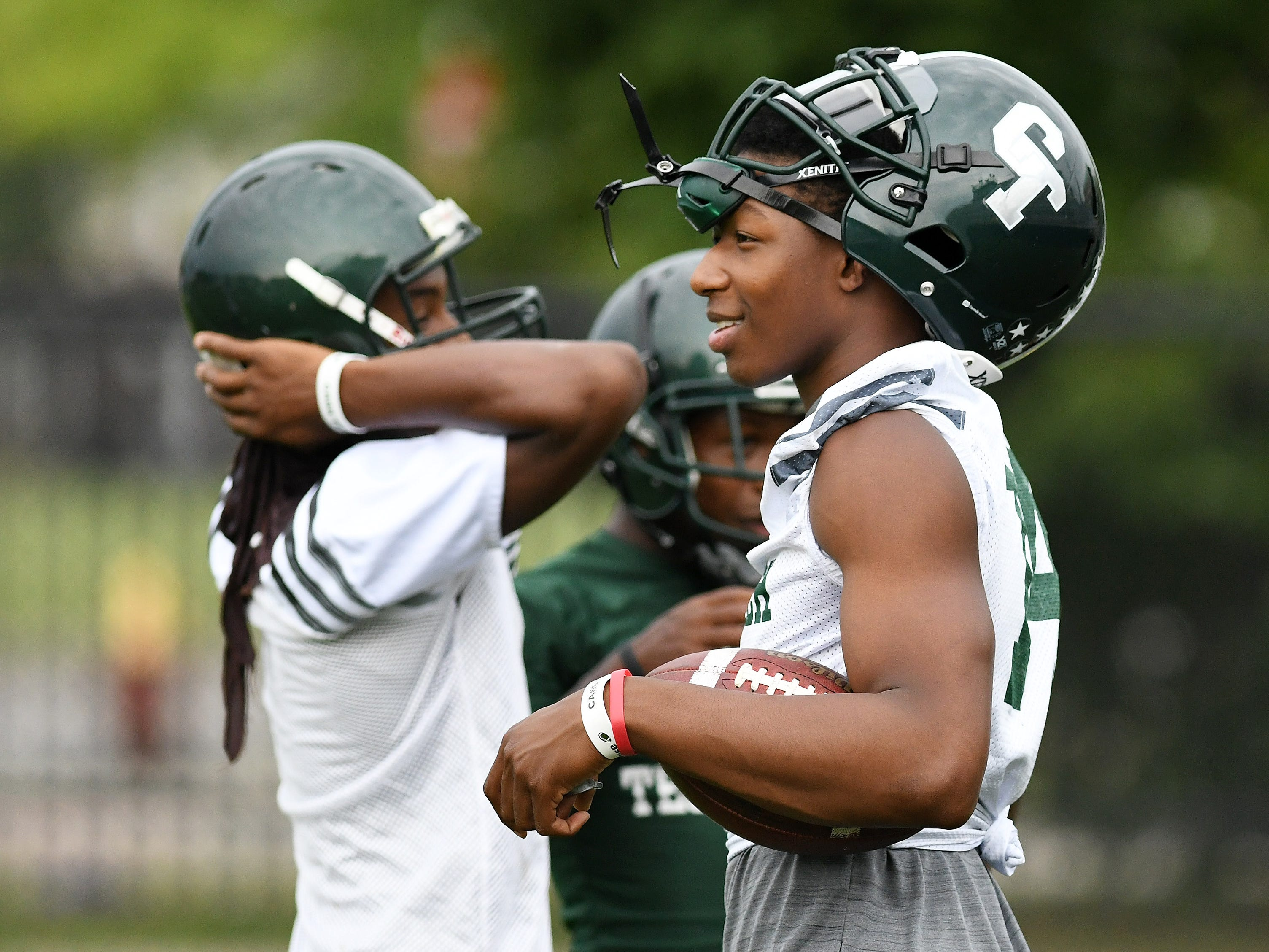 Quarterback Jalen Graham, right, at the start of football practice at Cass Technical High School in Detroit on Aug. 6, 2018.