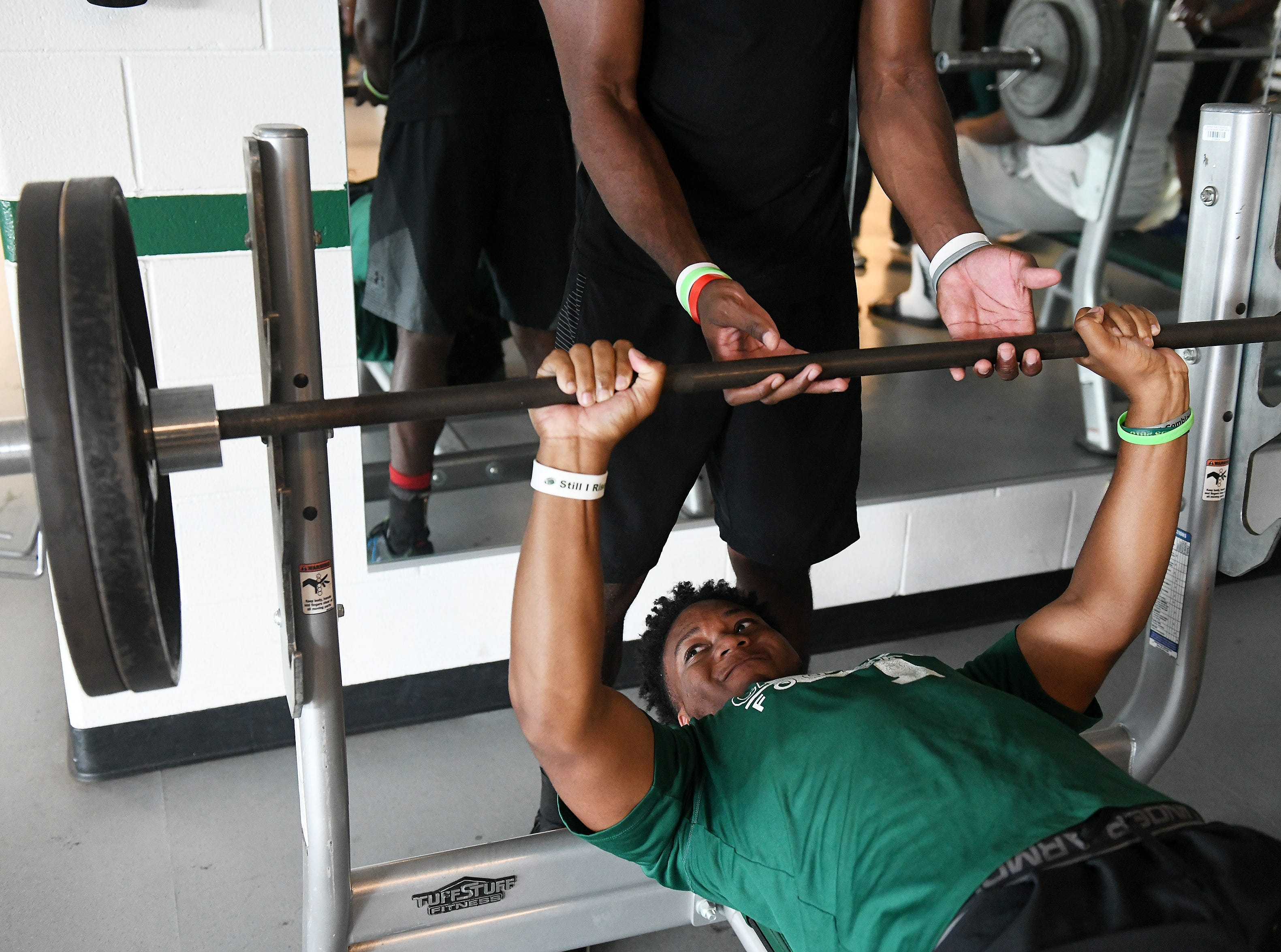 Detroit Cass Tech senior outside linebacker KeShon Parker bench presses during weight lifting before football practice.