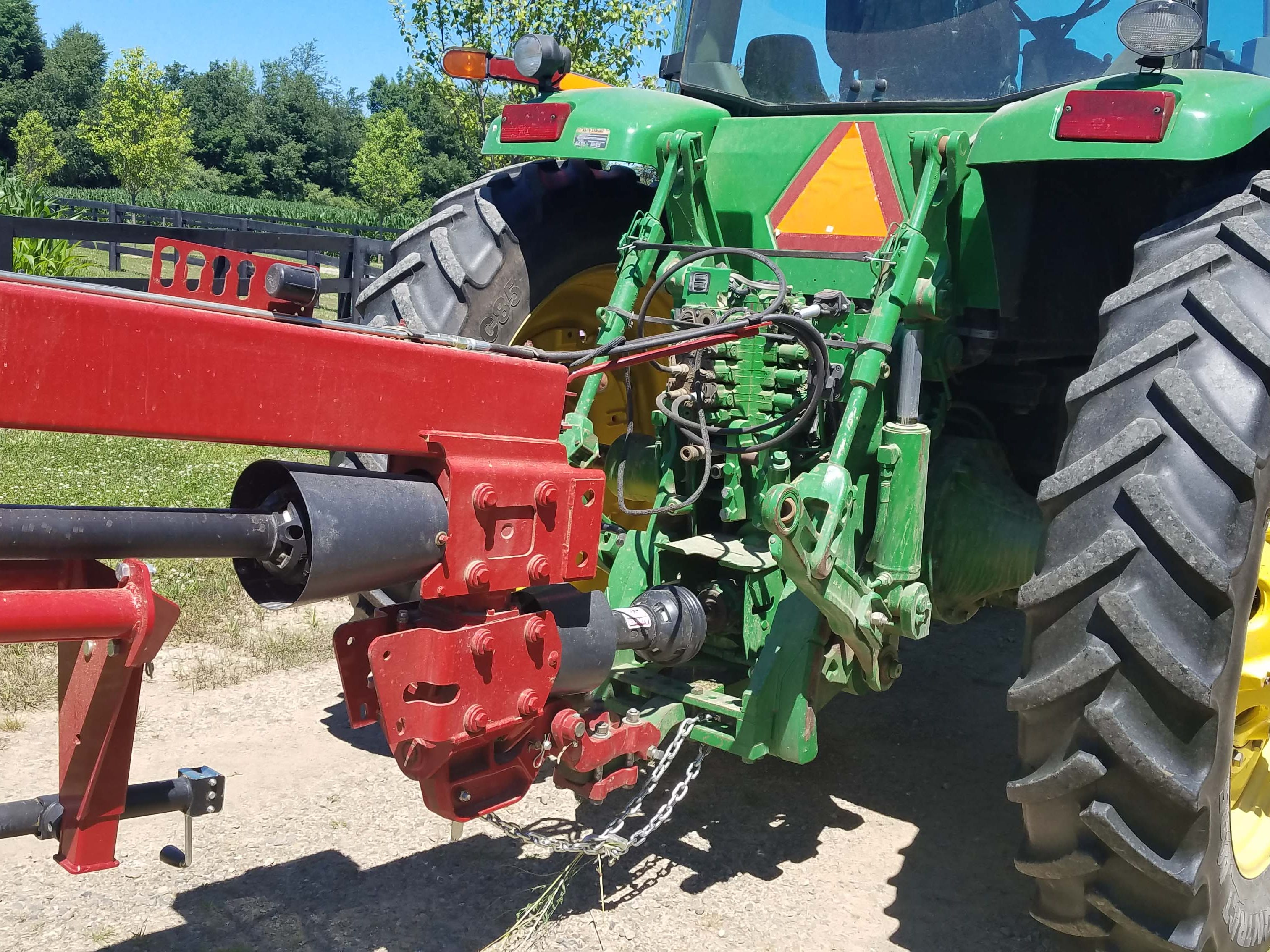 A large, slow John Deere tractor is hooked up to a grass-cutting farm accessory. The Lamborghini Nitro comes equipped for similar duty, but is also useful for front loader-equipped chores that need more speed.