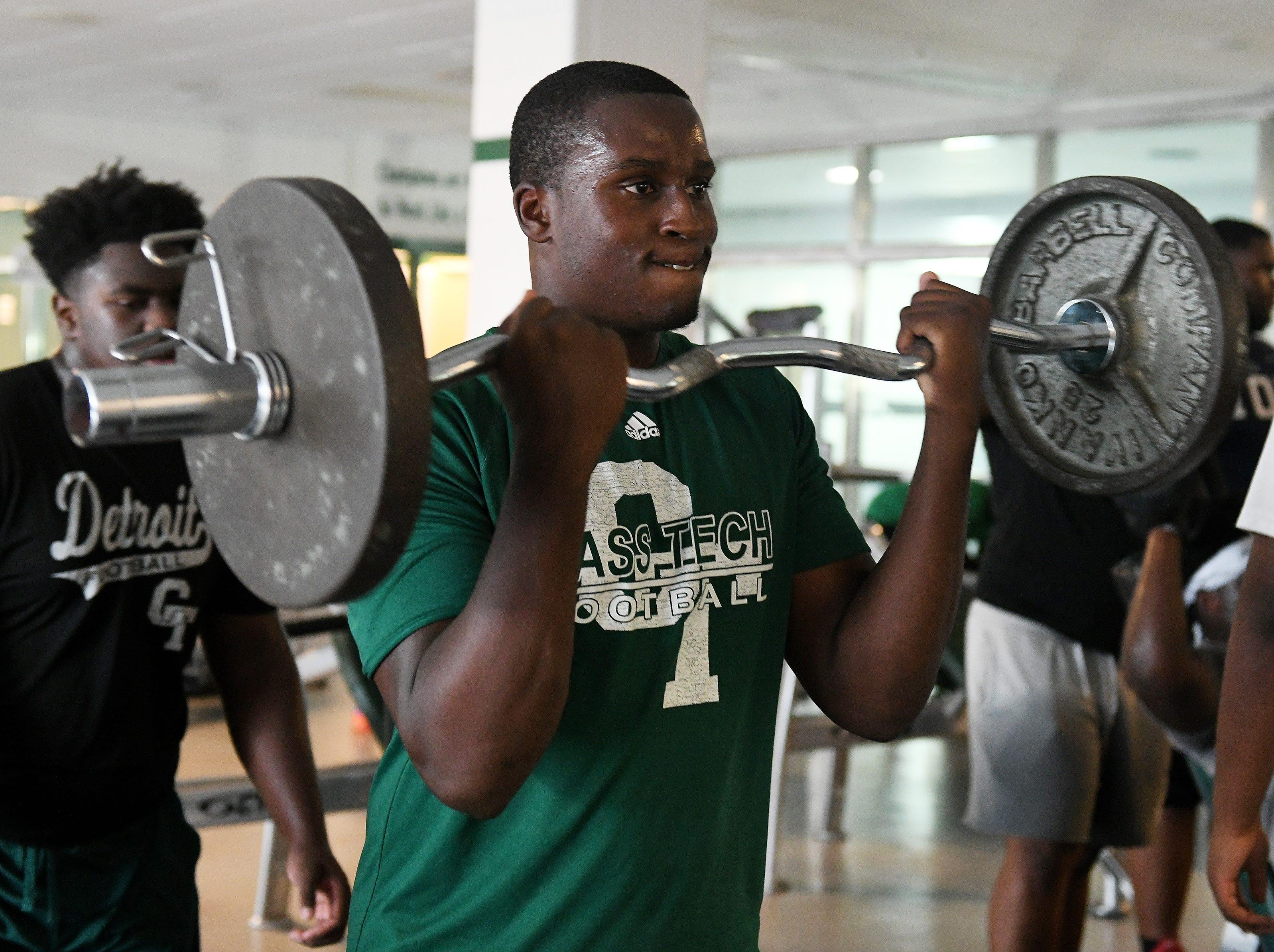 Detroit Cass Tech senior linebacker Bryce Martin does curls during weight lifting before football practice at Cass Tech High School.