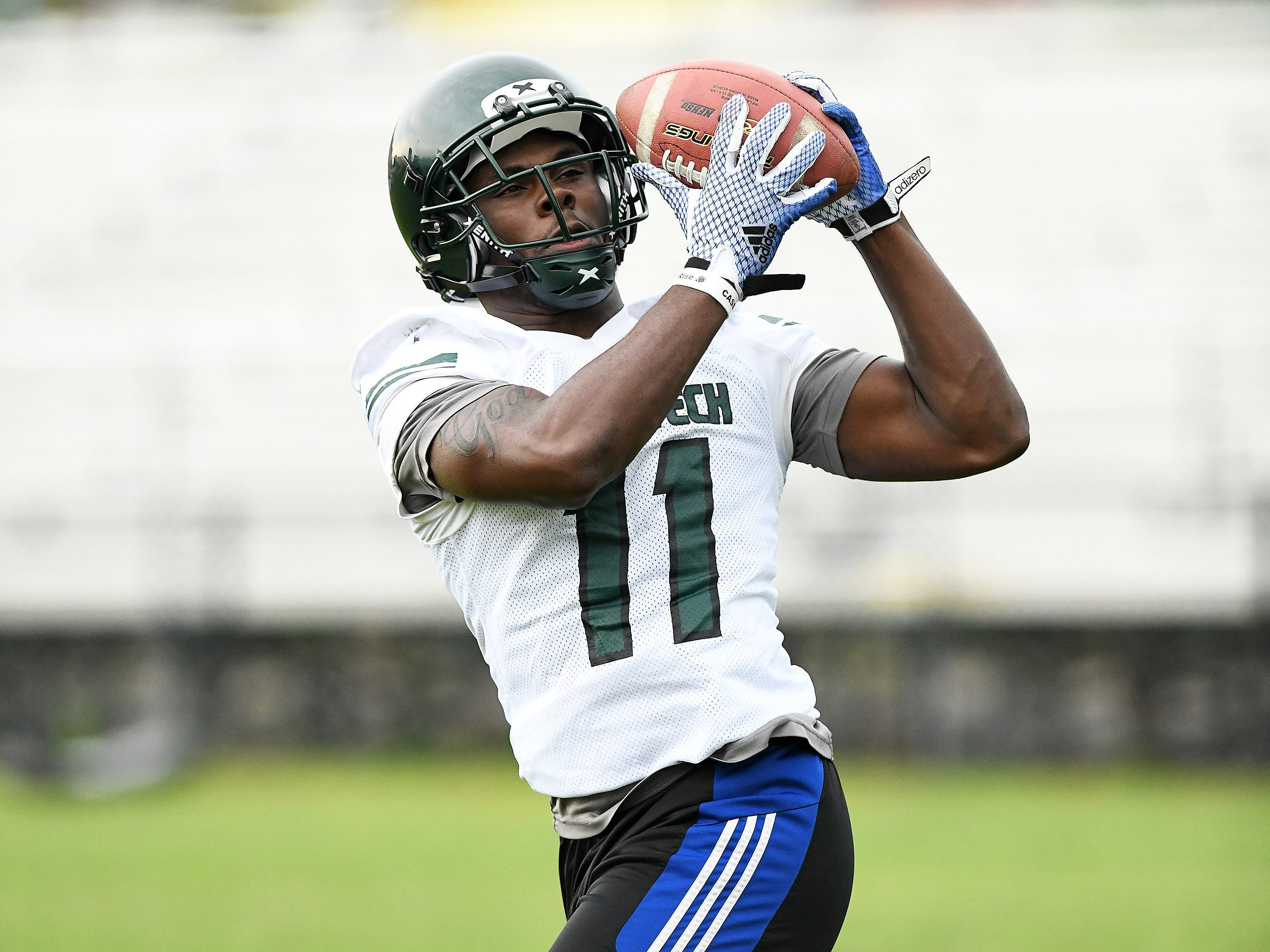 Running back Lew Nichols makes a catch during drills at football practice.