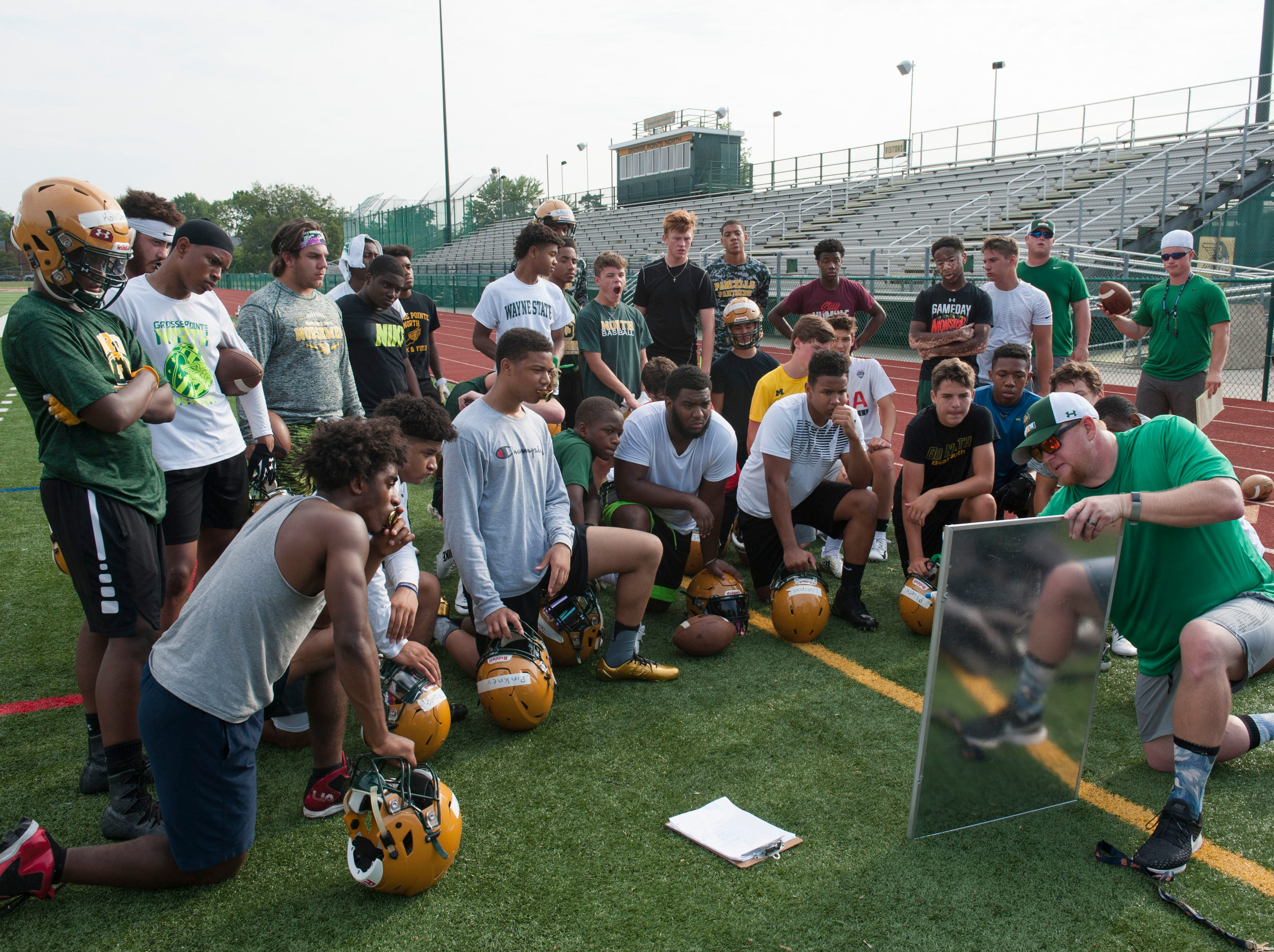 New assistant head coach/offensive coordinator Dennis Pascoe draws up some offensive plays on a white board with the Grosse Pointe North football players gathered around him at their first practice of the season.