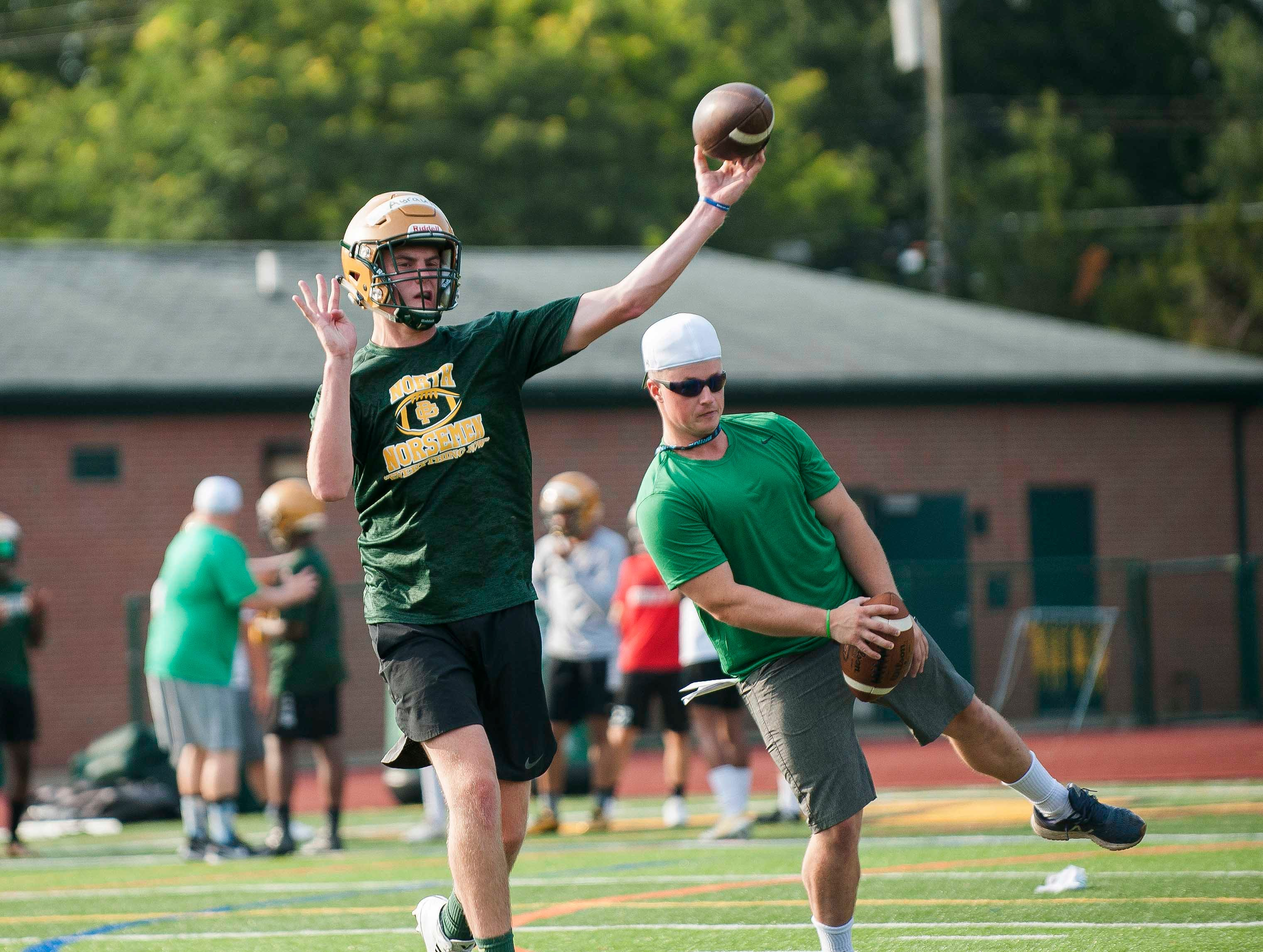 Quarterback Joe Ayrault throws a pass with quarterbacks coach Hannibal Roda (right) following his movements during the first practice of the season.