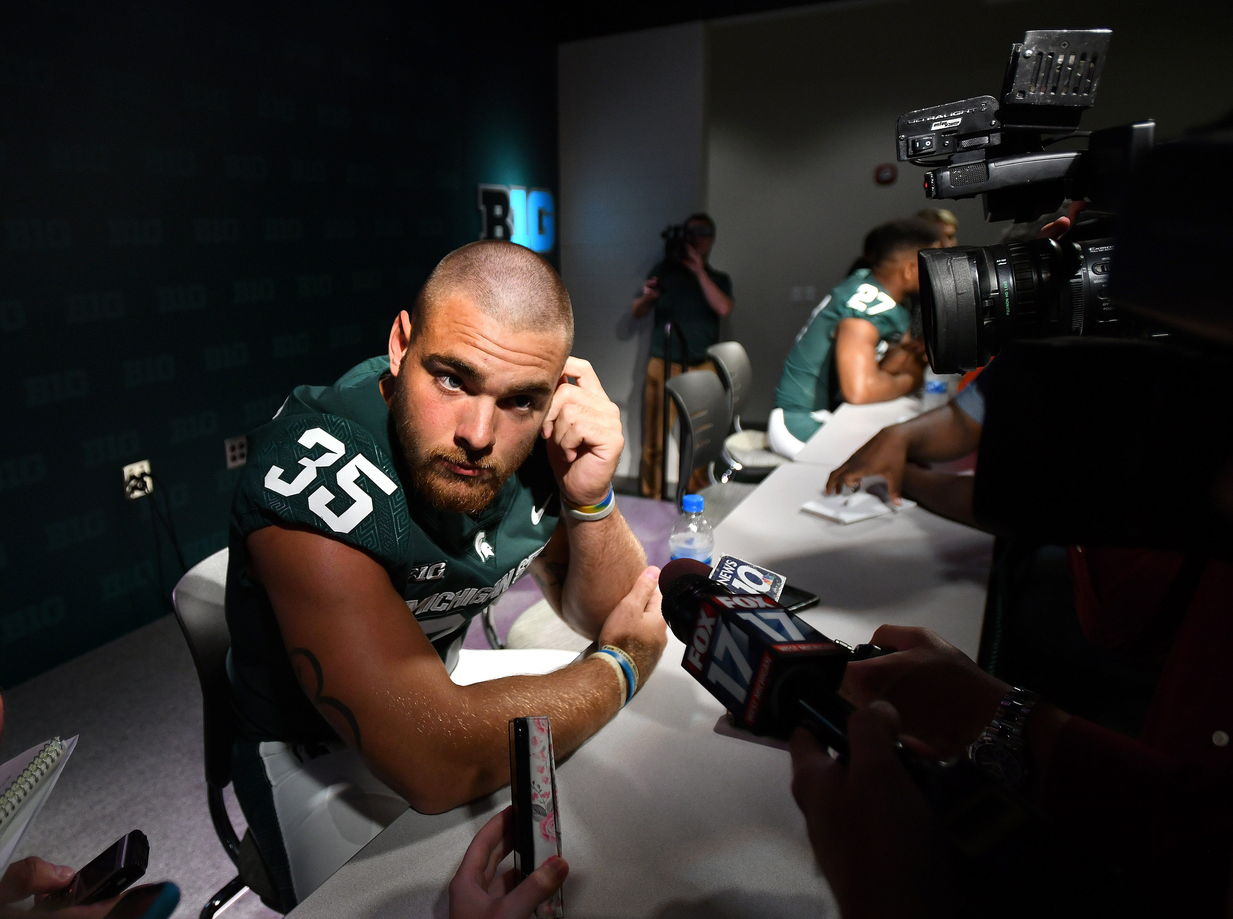 Michigan State linebacker Joe Bachie struggles to hear a question posed by a reporter amid the din of media day.