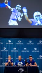 Memorial High School's Michael Lindauer, left, Coach John Hurley, center, and Branson Combs address the media at the 2018 High School Media Day. A photograph of Lindauer throwing a pass during the 2017 state championship run is projected above the trio.