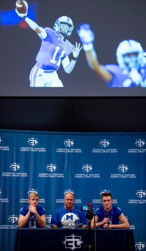 Memorial High School's Michael Lindauer, left, Coach John Hurley, center, and Branson Combs address the media at the Courier & Press High School Media Day at Milestones Monday morning. A photograph of Lindauer throwing a pass during last year's state championship run is projected above the trio.