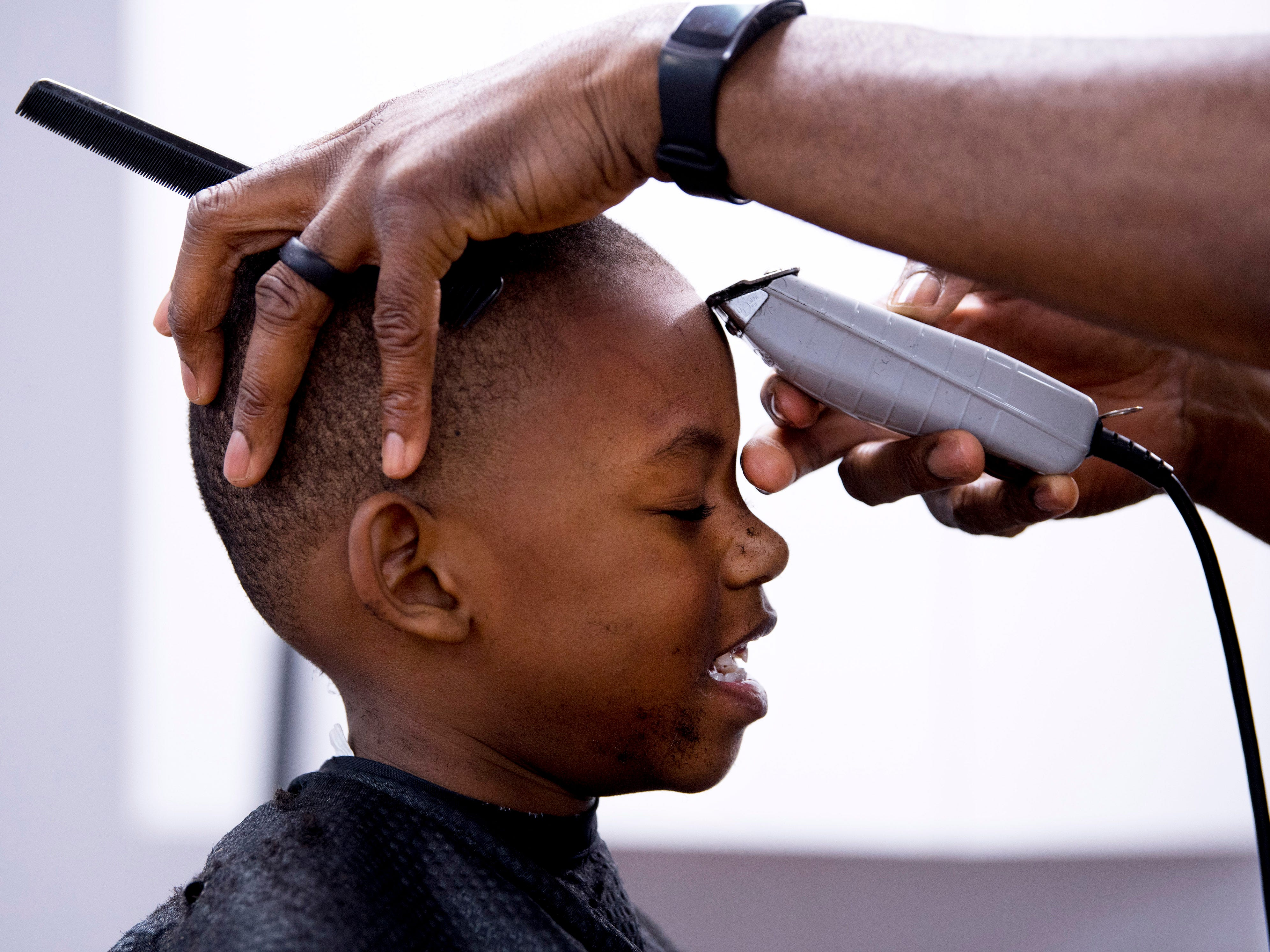Javien Watt, 6, gets the finishing touches on his new haircut by Jerald Taylor at Jerald's Barbershop Monday morning. Tyler and barber Demetrius Fingers volunteered their day off to help out area youngsters with free hair cuts in preparation for their first day of school this Wednesday. The business partnered with Young and Established, a youth mentoring group, to help the kids out. Although the barbers were only scheduled to cut from 8 a.m. - noon, they were still working well after that with about 20 more kids waiting their turns.