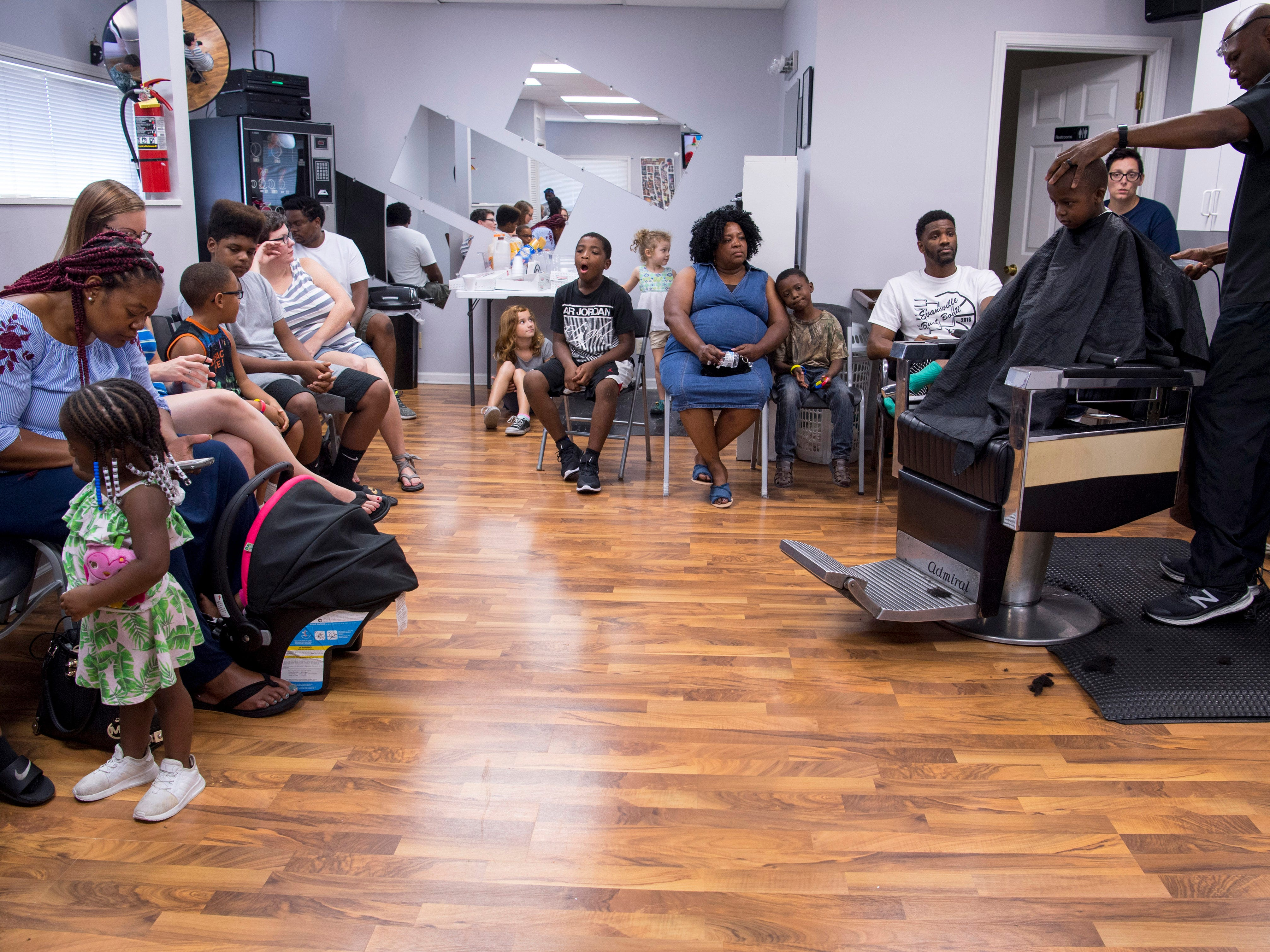 Families wait their turns for barbers Jerald Taylor and Demetrius Fingers (not pictured) to call their names for free haircuts at Jerald's Barbershop Monday.