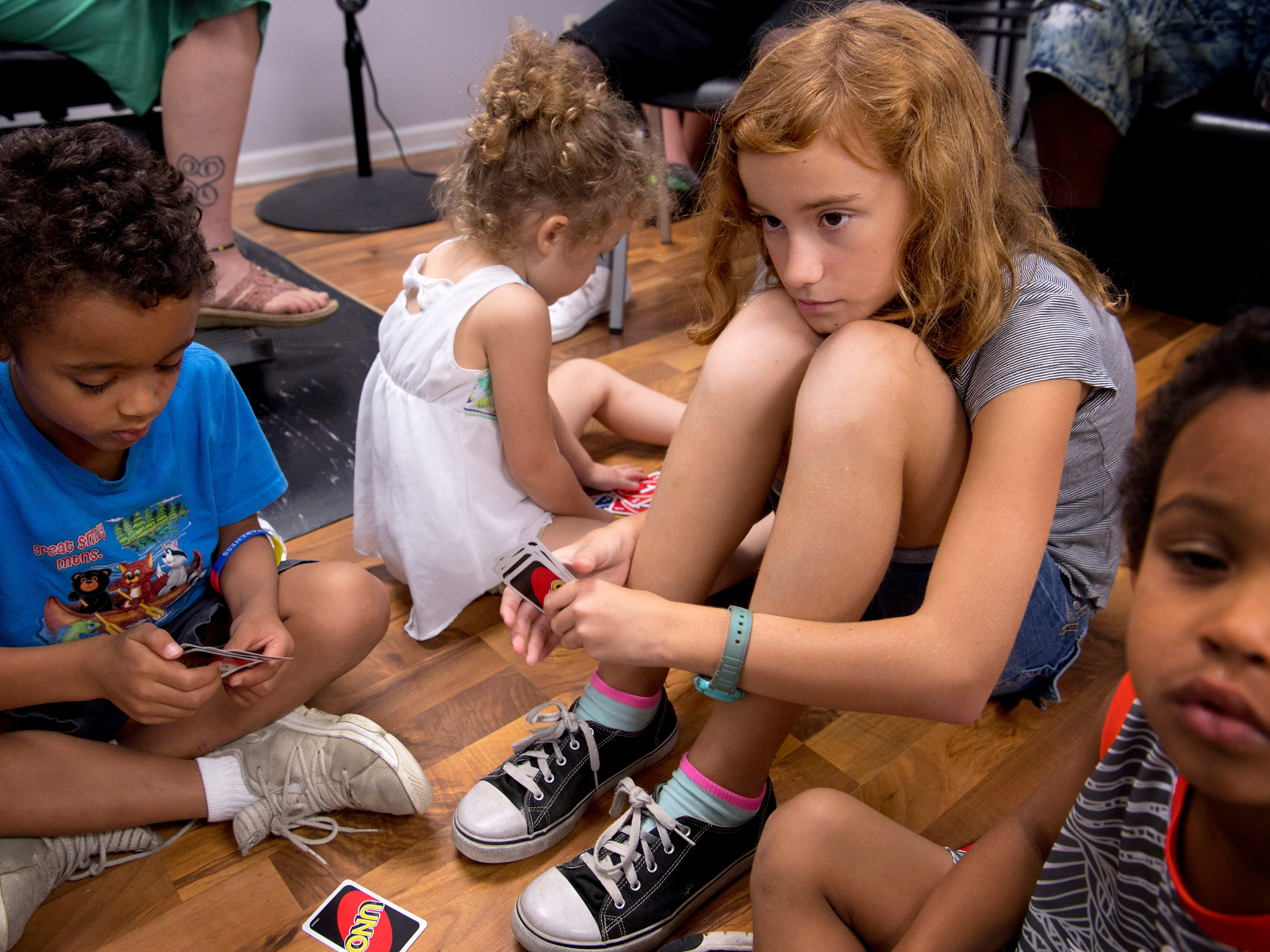 Layla Whitepeacock, 11, right, waits for her opponent, Cassius Thomas, 6, left, to make a play during their game of Uno at Jerald's Barbershop Monday morning. The kids were waiting for their turns for free back-to-school haircuts.