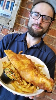 Chef Noel Bilbro of Maidens Brewery and Pub with a plate of his beer battered haddock, fresh cut Kennebec chips, and superfood slaw.