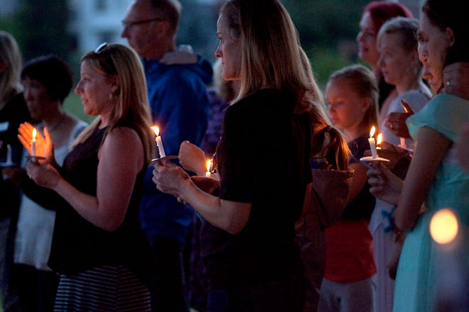 Family and friends mourn the loss of Cross Goodwin during a candlelight vigil held at Fossil Creek Park Sunday evening.