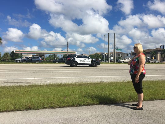 Connie Bires held her hand to her heart as she watched the procession for the funeral of FMPD officer Adam Jobbers-Miller drive by on Colonial Boulevard.