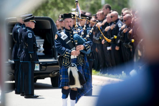 A bagpiper from the North Port Police Department plays Amazing Grace at the funeral  of Fort Myers Police Officer Adam Jobbers-Miller on Monday, August 6, 2018, at Germain Arena in Estero.