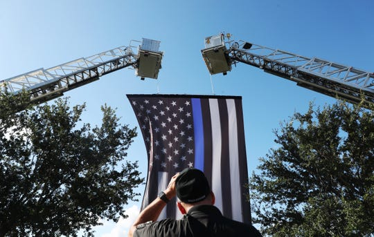 A thin blue line flag was erected in honor of fallen Fort Myers police officer Adam Jobbers Miller on Monday.