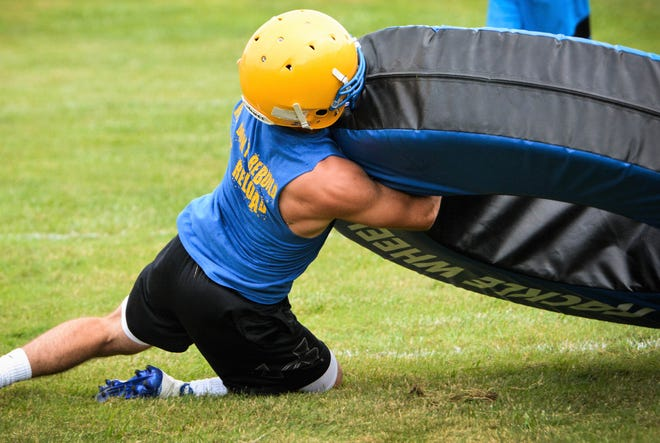 Bennett Frazer practices tackling at an Oconto football practice on Friday.