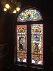 A stained glass window along the stairs at the Copper King Mansion in Butte. The chandelier is designed for electric and gas lights.