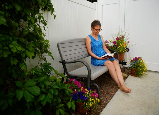 Colleen Davis-Ryan enjoys reading on her patio.  Colleen used natural heath care modalities in addition to traditional chemo therapy in battle with breast cancer.