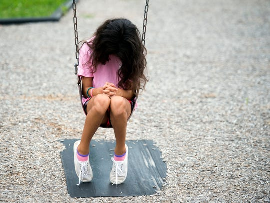 Rebekah Spierdowis offers a prayer while on the playground swing at Corryton Elementary School on Sunday, August 5, 2018.