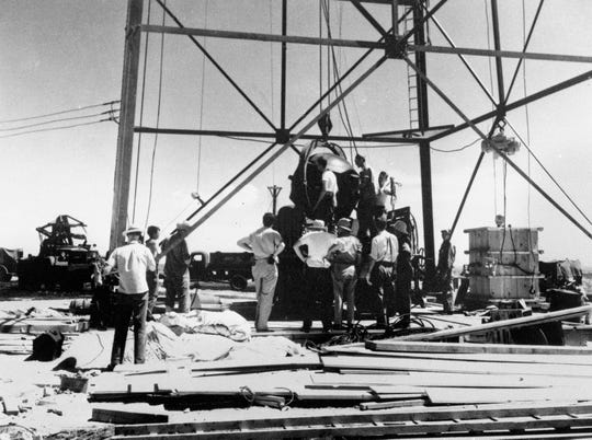 FILE - In this July 6, 1945, file photo, scientists and workmen rig the world's first atomic bomb to raise it up onto a 100 foot tower at the Trinity bomb test site near Alamagordo, N.M. (AP Photo/File)