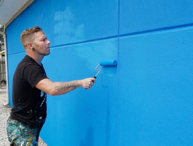 Cameron Moberg touches up a few spots of a blue base layer he is painting on the side of Habitat for Humanity of Lafayette's offices Monday, August 6, 2018, at 420 S. 1st Street in Lafayette. Local artist Mitchell Schuring will paint a mural on the wall. Moberg will be painting a dove on the side of Sacred Grounds as well as leading a collaborative effort of artists painting murals just below the railroad overpass on Wabash Avenue.