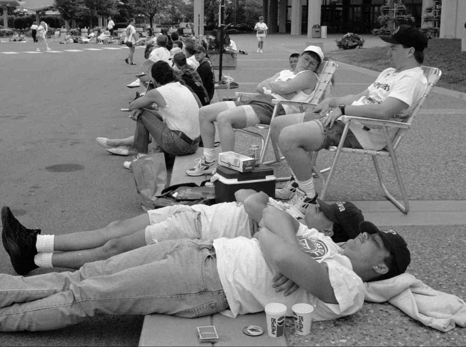 Waiting for ticket sales to begin at the Fairgrounds for 1995 Kentucky State Fair concerts (most, if not all, of these people are country music fans).  Sleeping along the curbside are Bob Parker (fore) and Marco Oliverio, both of Cincinnati.  They were interested in George Strait tickets.