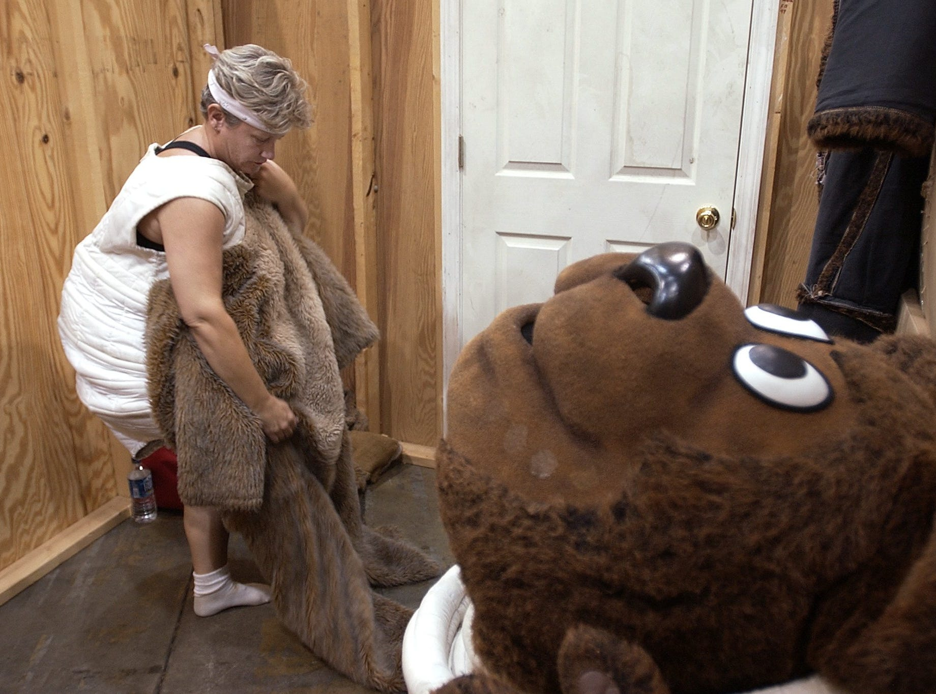 Carolyn Hensley puts on the the Faira Bear costume inside the Fairbear clubhouse at the fairgrounds.-