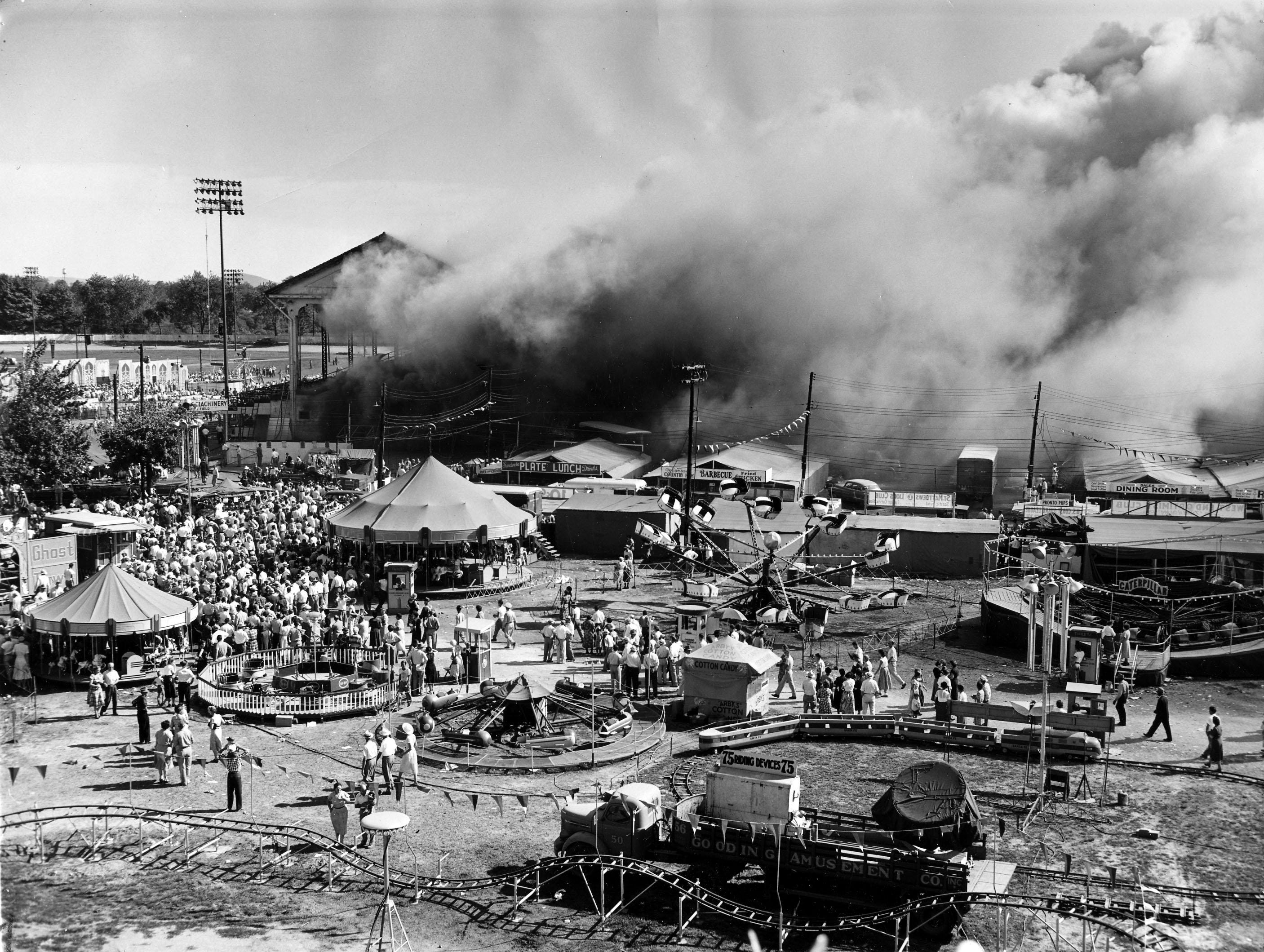 Smoke pours from the grandstand but the midway rides and the water carnival, far left in front of grandstand, are in bright sunshine. The rides stand idle because of the greater attraction of the fire. The State Fair Board was meeting in its office building at the Fairgrounds when the fire broke out.