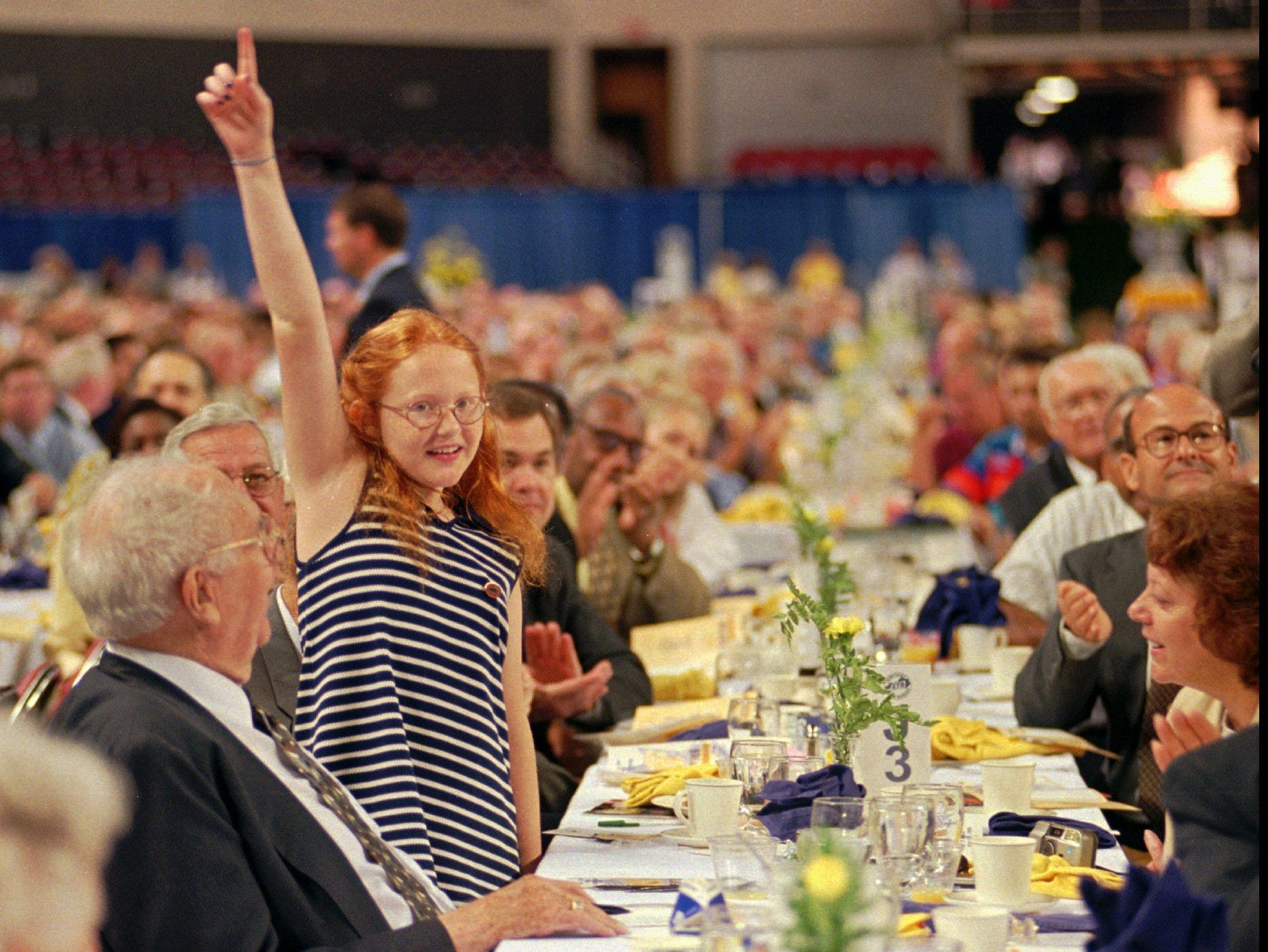 Maggie Hitron, 10, bankrolled by her grandfather, Louisville developer Al Schneider, left, cast the winning bid of $3,000 a pound for this year's grand champion ham at the 35th annual Kentucky Country Ham Breakfast in Louisville. The 15.9-pound ham was exhibited by Frank Dulin Jr. of Pembroke.-