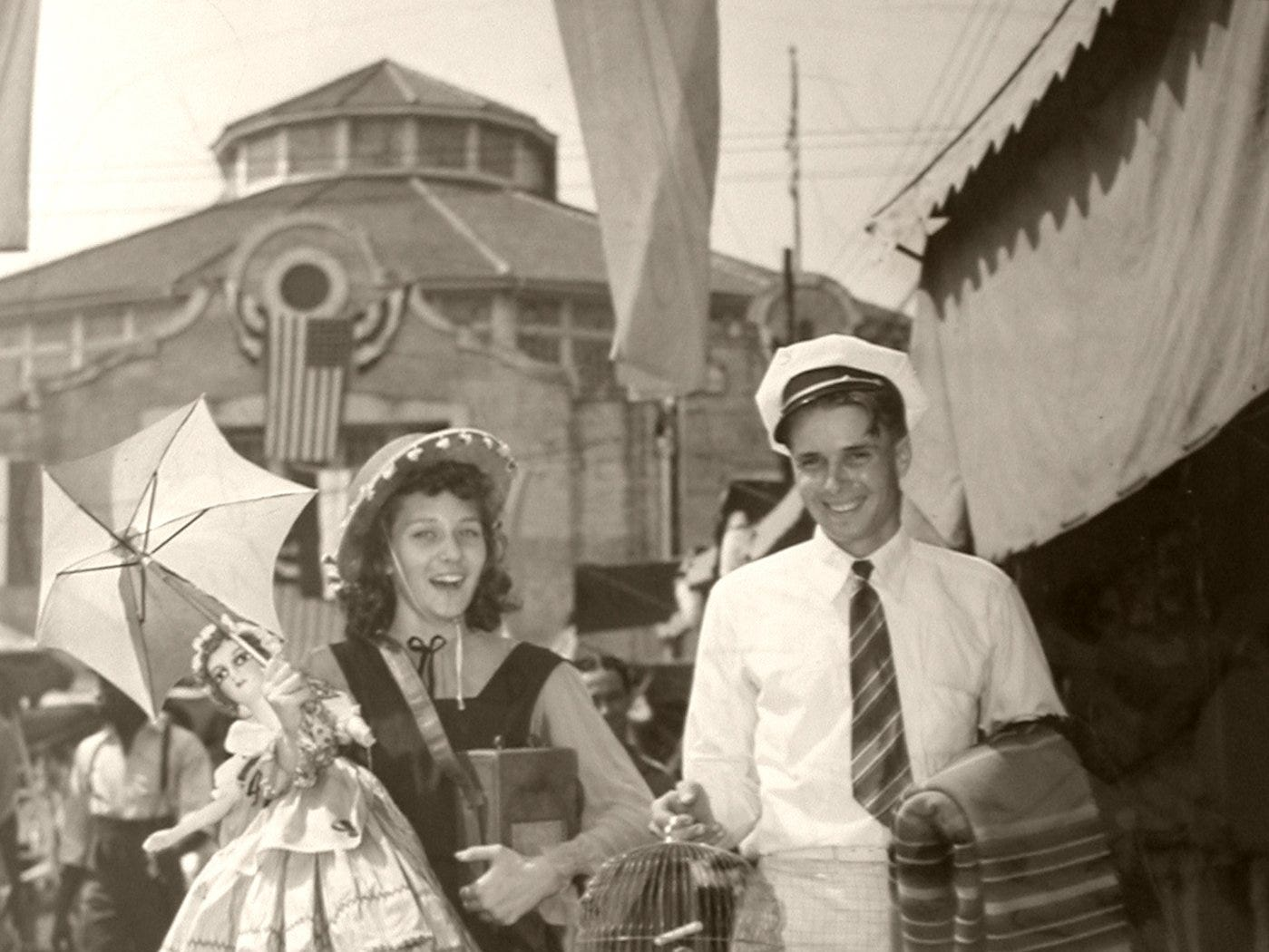 Waltrude Tichenor of Hartford, Ky., and Bob Russell of Utica, Ky., walked along the Kentucky State Fair Midway in 1939, toting a host of prizes they won at the booths.
