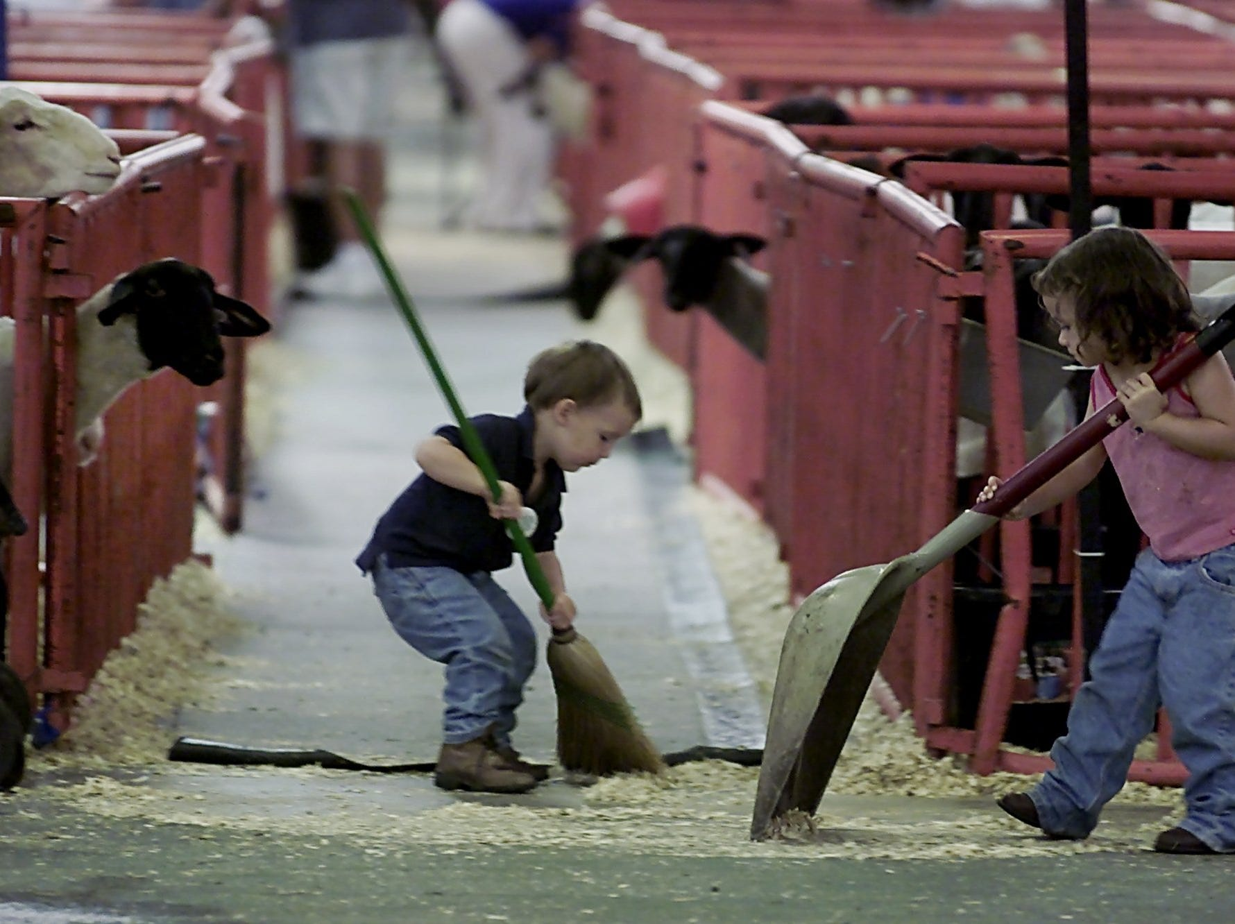 T.J. Yazell, 2, left, and his sister Haleigh Yazell, 3, of Bourbon County, had the duty to clean up around their family's sheep stalls at the state fairgrounds after the fair closed.-