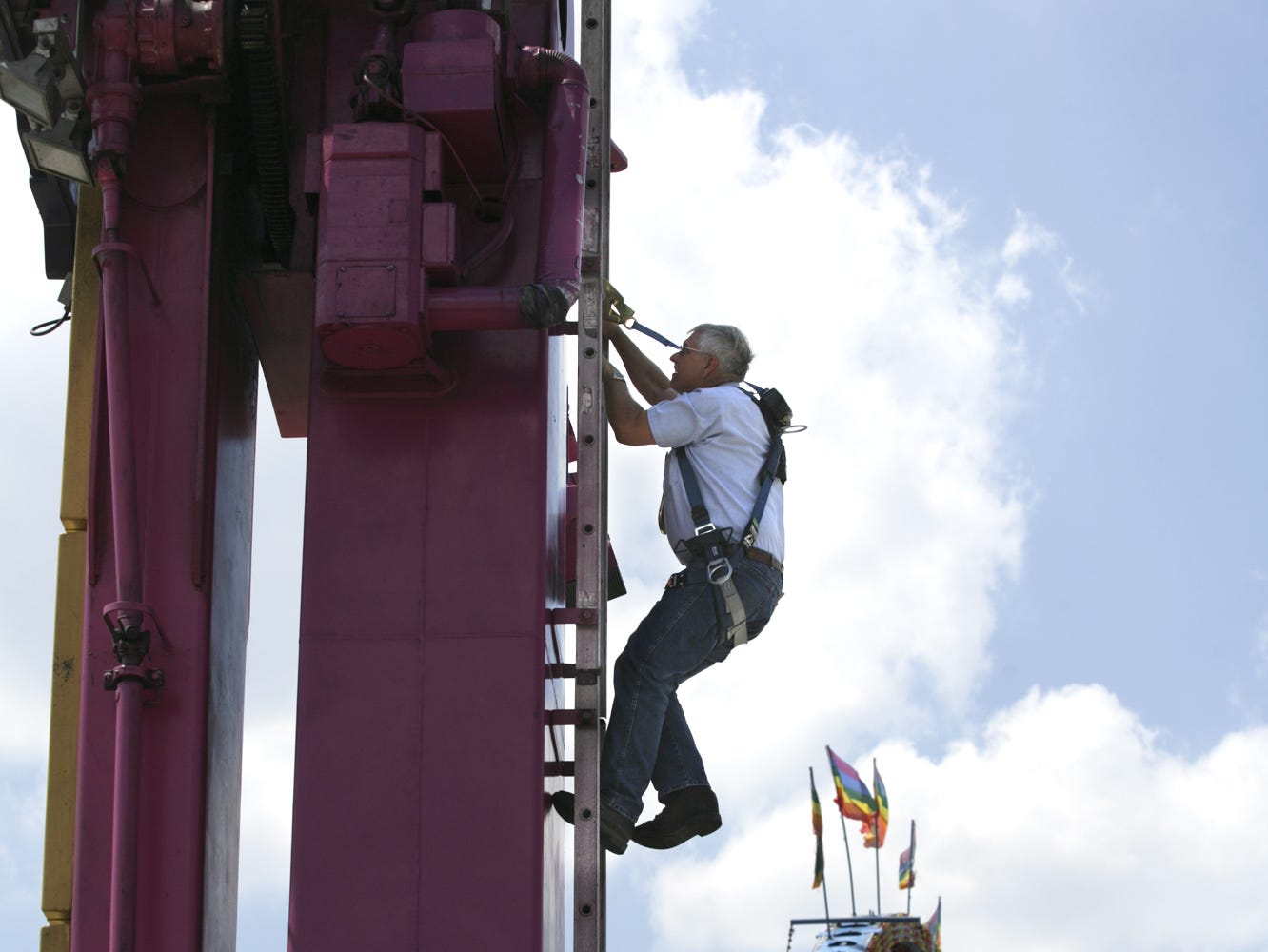 Bob Henderson, a state fair ride inspector, used climbing gear to reach the upper parts of the Inverter ride.  He was one of 10 inspectors who had to approved 43 rides before the state fair opened on Thursday.