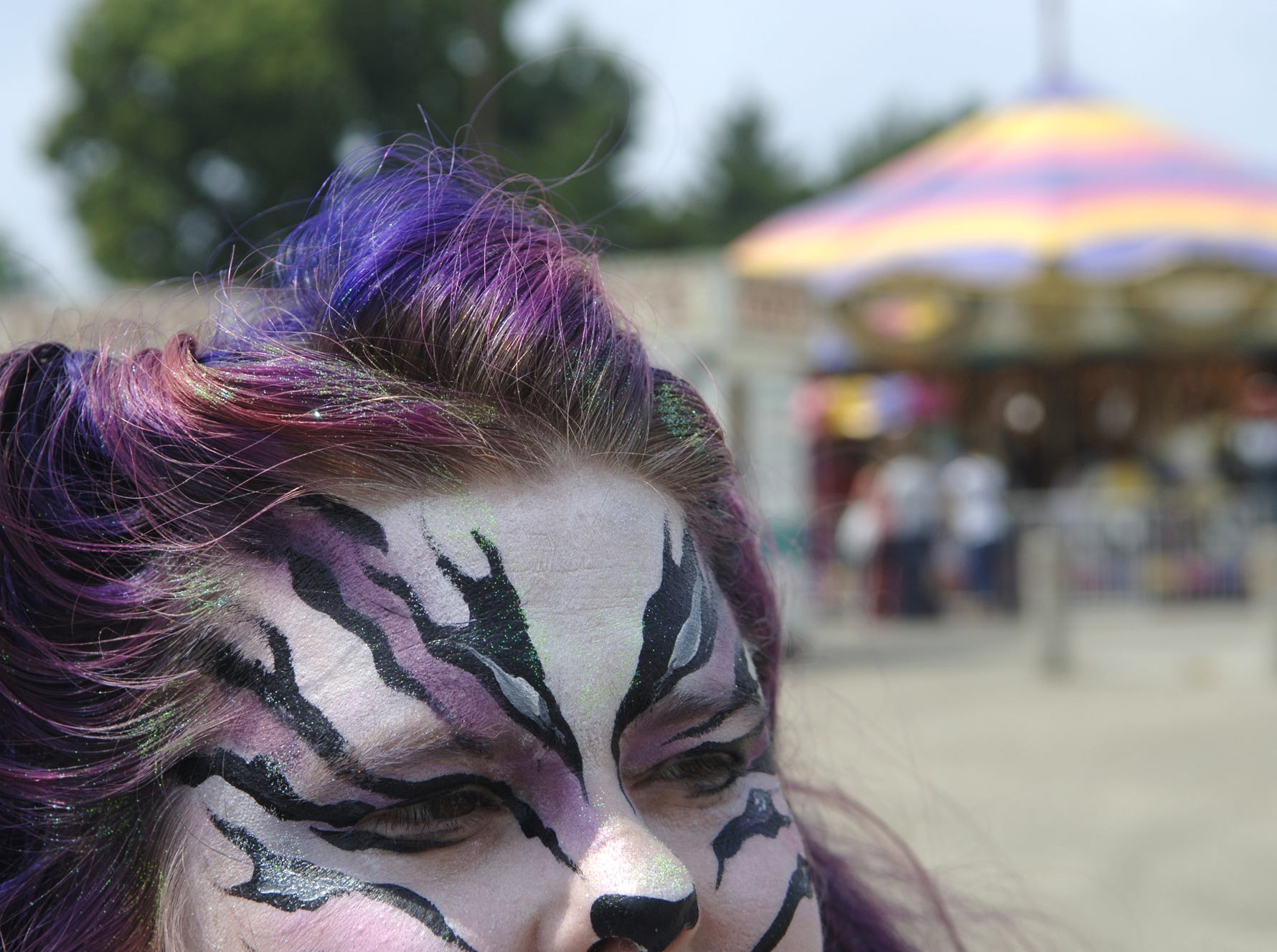 Louisville resident Melissa DePlanche had her face painted to match her hair as she sat near the midway at the Kentucky State Fair.