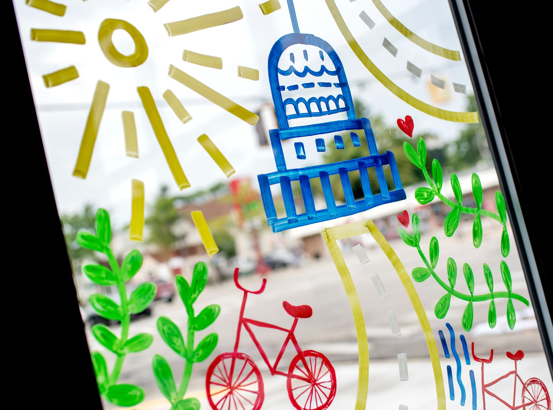 Artwork promoting 'Imagine the Avenue' covers the windows on Monday, Aug. 6, 2018, at The Venue on Michigan Avenue in Lansing. From Aug. 6-11, the 2000 block of Michigan Avenue will be displaying temporary street design changes including protected bike lanes, expanded sidewalks and enhanced bus stops.