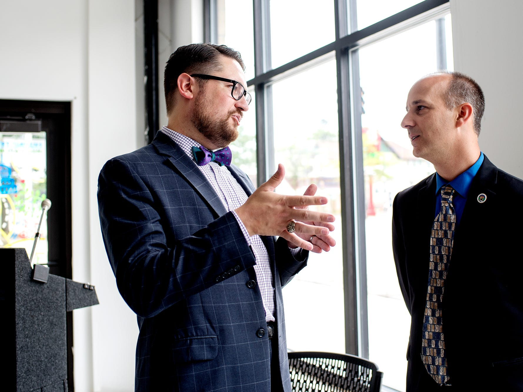 Mayor Andy Schor, right, speaks with CATA chairperson Nathan Triplett after a press conference kicking off 'Imagine the Avenue' on Monday, Aug. 6, 2018, at The Venue on Michigan Avenue in Lansing.