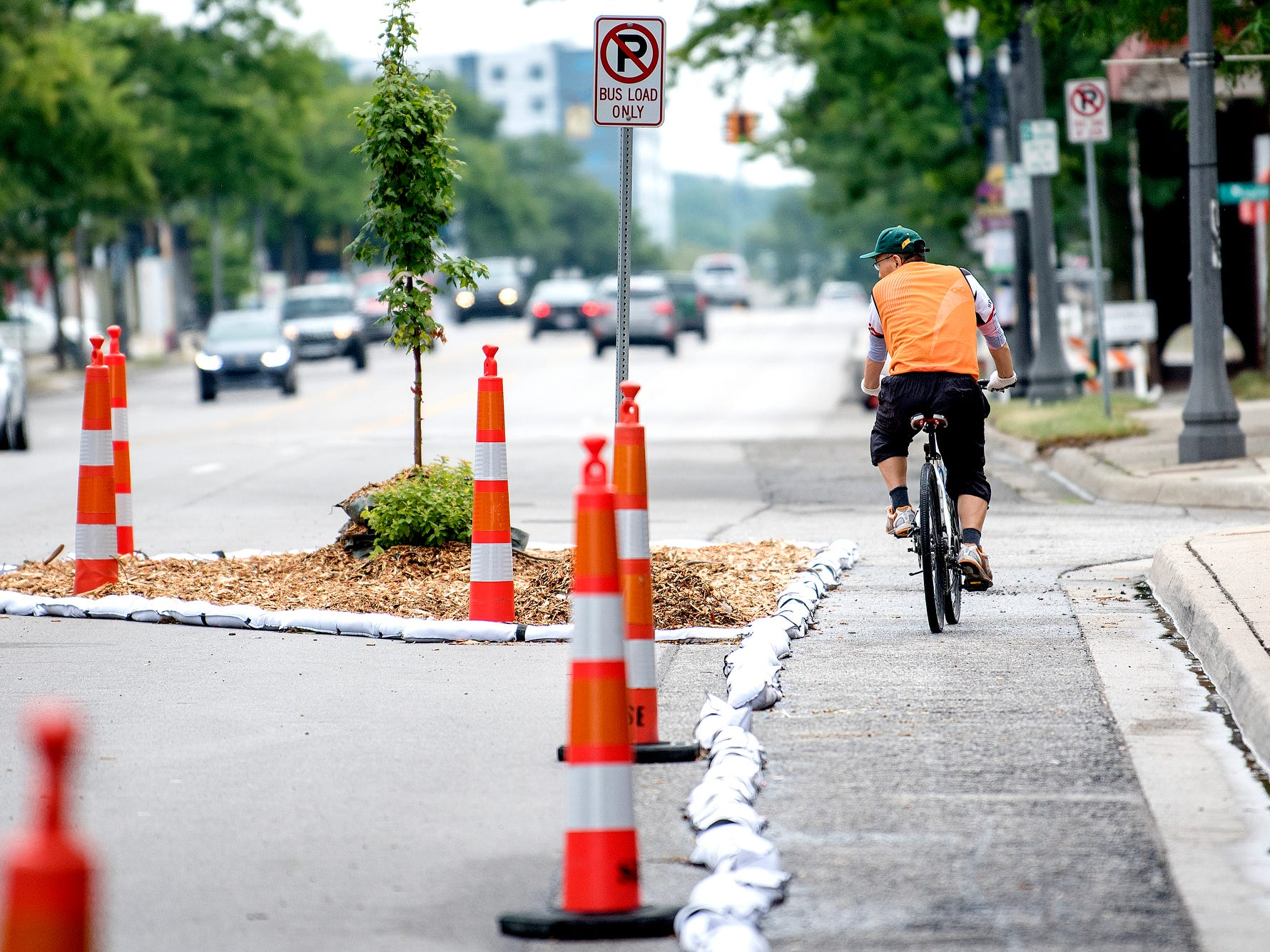 A bicyclist makes his way down a temporary bike lane as part of 'Imagine the Avenue' on Monday, Aug. 6, 2018, at The Venue on Michigan Avenue in Lansing.